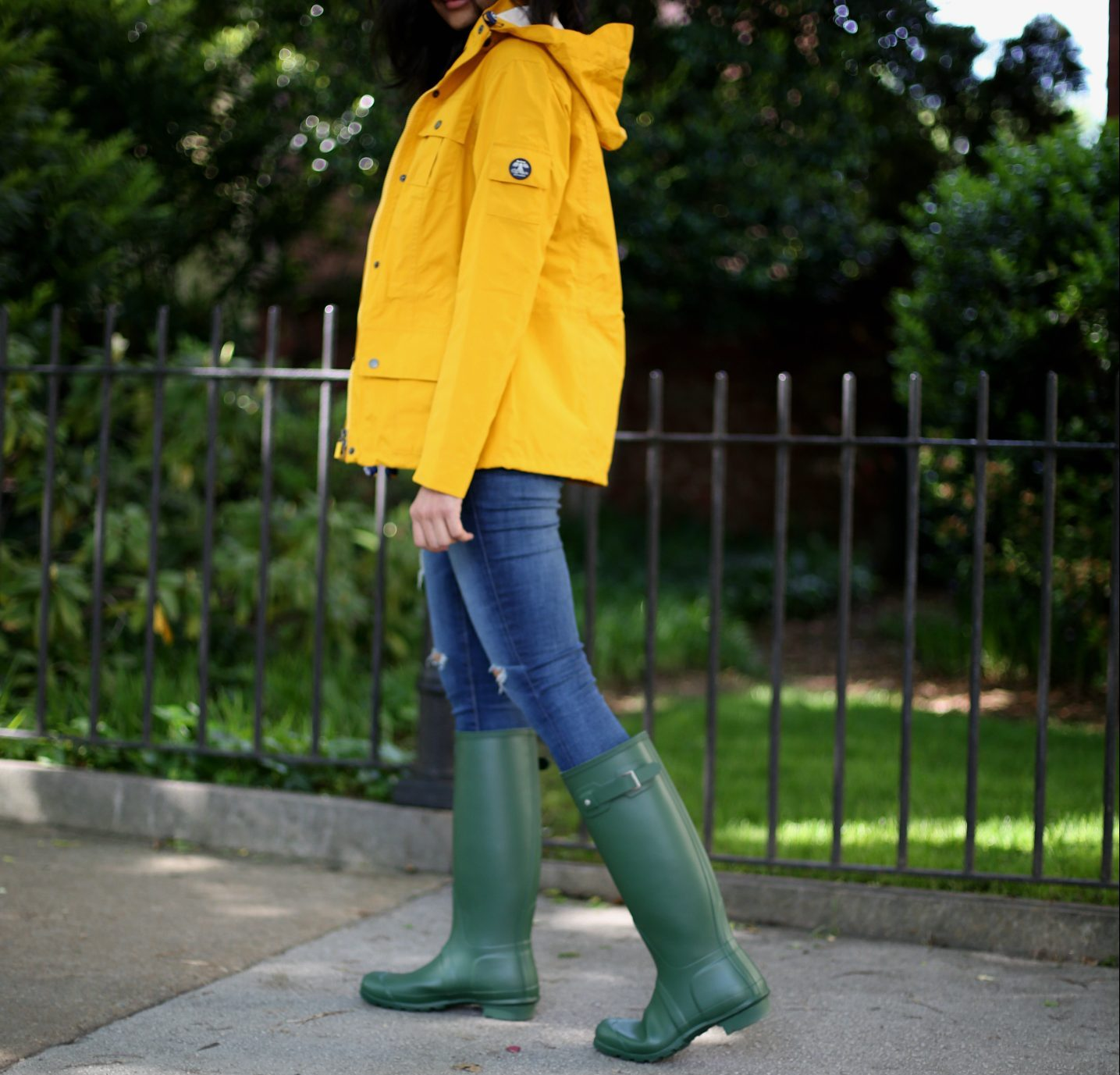 barbour-yellow-rain-jacket-dl | Lightweight Jackets by popular Maryland modest fashion blog, Dreaming Loud: image of a woman wearing a yellow rain jacket with jeans, and green knee high rain boots.