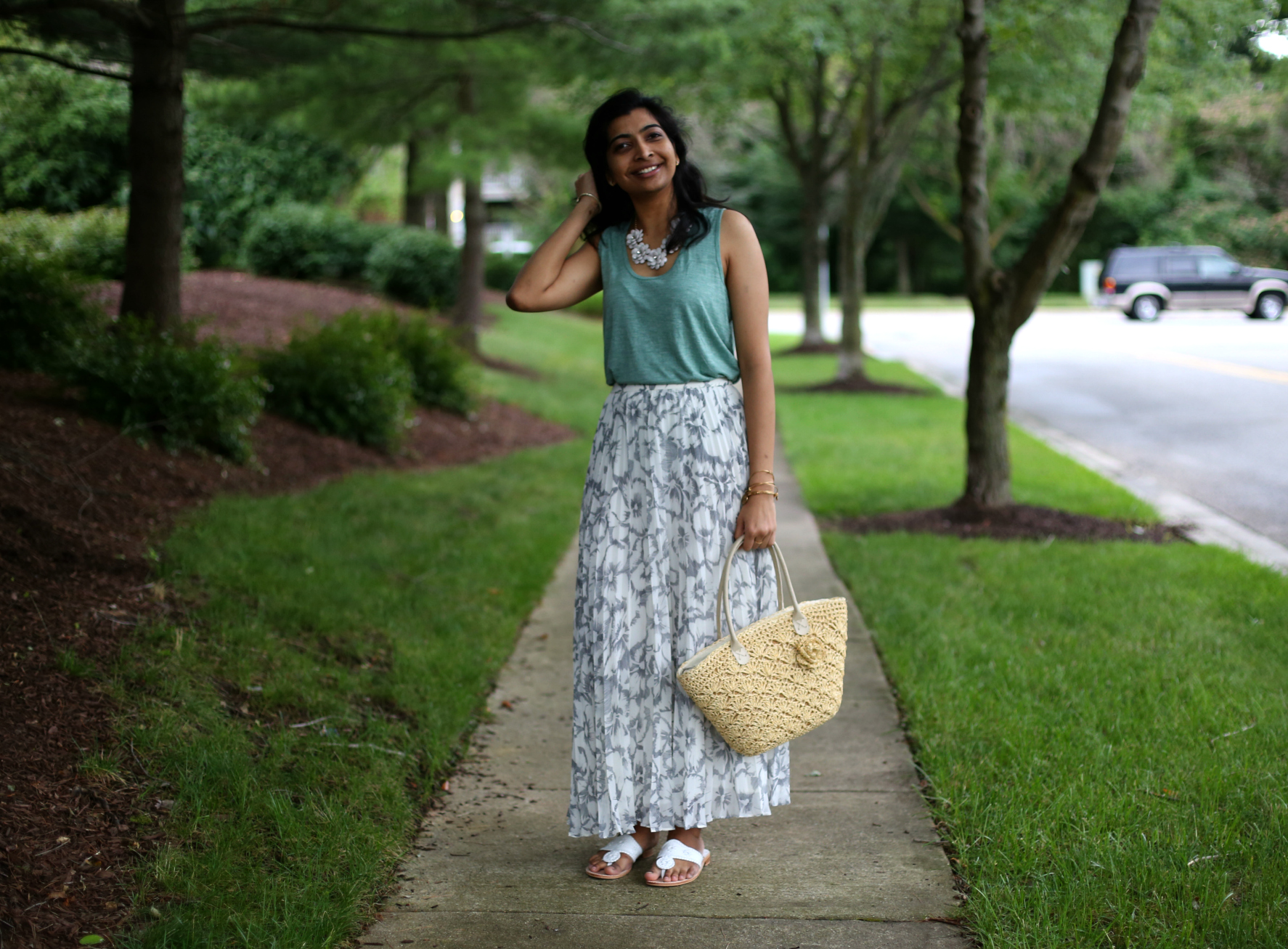 Summer Essentials for Women featured by top US modest fashion blog, Dreaming Loud: image of a woman wearing a madewell Whisper Cotton Crewneck Muscle Tank, floral skirt, straw tote, Jack Roger Sandals