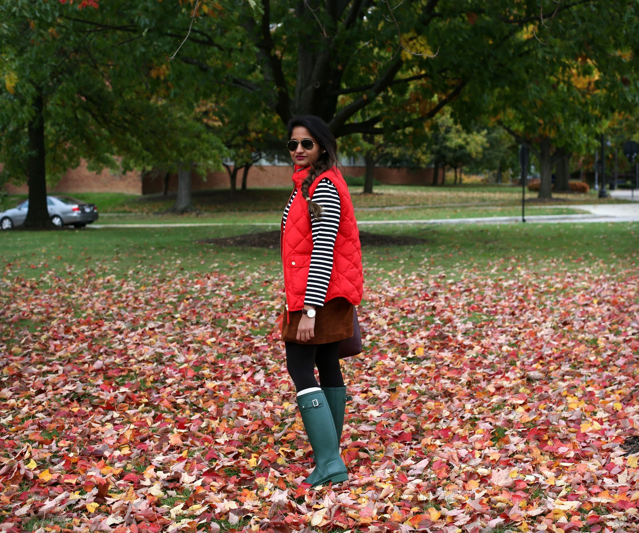 Lifestyle Blogger Surekha of Dreaming Loud Wearing Suede skirt and red puffer vest