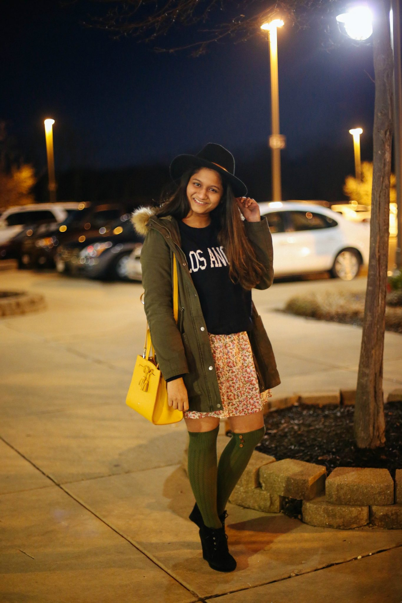 How to to wear utility parka |Utility Jackets by popular Maryland modest fashion blog, Dreaming Loud: image of a woman wearing a utility parka with black felt hat, green knit over the knee socks, floral skirt, black Los Angeles shirt and black suede ankle boots.