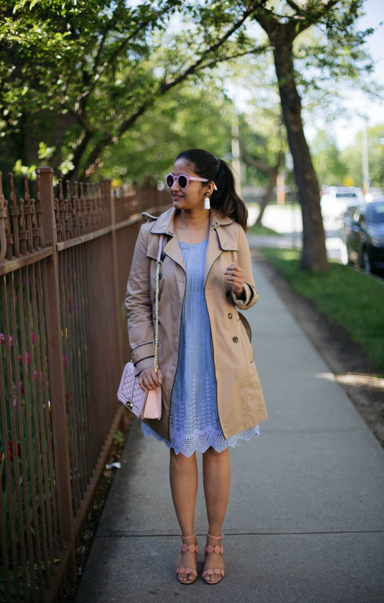 macys-style-and-co-eyelet-hem-fit-and-flare-dress | Lightweight Jackets by popular Maryland modest fashion blog, Dreaming Loud: image of a woman wearing a tan cotton twill jacket, blue eyelet hem dress, white statement earrings, tan strap sandals, and pink quilted purse.