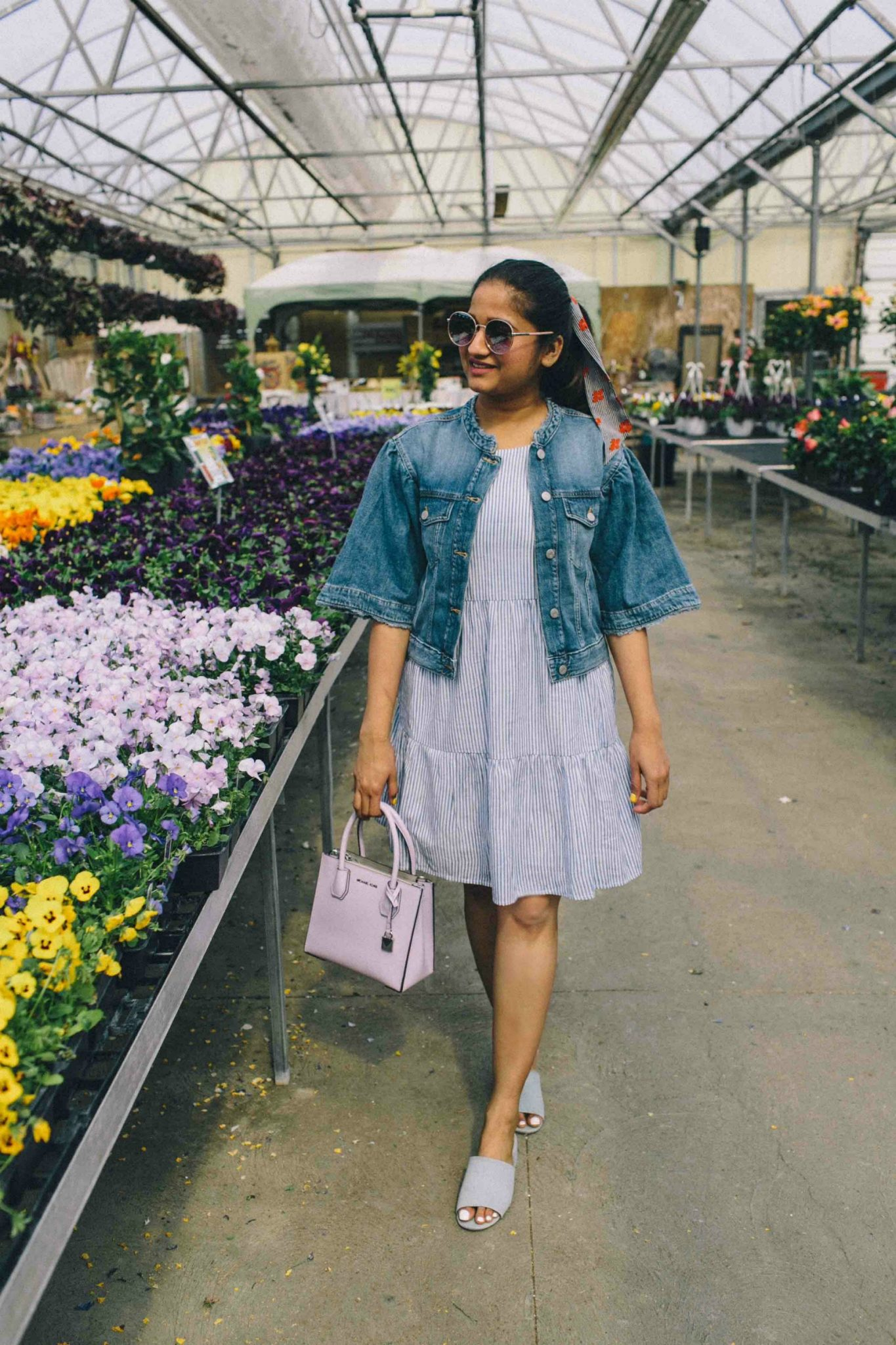 how to wear or style bell sleeves cropped denim jacket | Lightweight Jackets by popular Maryland modest fashion blog, Dreaming Loud: image of a woman standing near some flowers in a green house and wearing. cropped denim jacket with a grey and white stripped dress and grey block heel open toe mules.