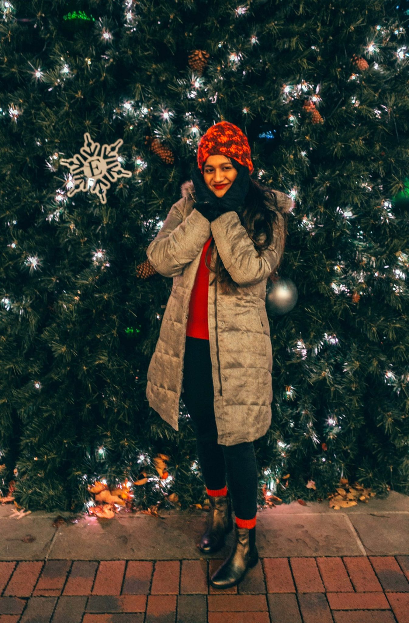 Causal red Christmas outfit ideasEddie Bauer puffer jacket for Winter featured by top US fashion blogger, Dreaming Loud: image of a woman in front of a Christmas tree, wearing an Eddie Bauer puffer jacket, Eddie Bauer women's gloves, Eddie Bauer red beanie, J.Crew red sweater, Aetrex metallic booties, thermal winter socks and Madewell high rise skinny jeans