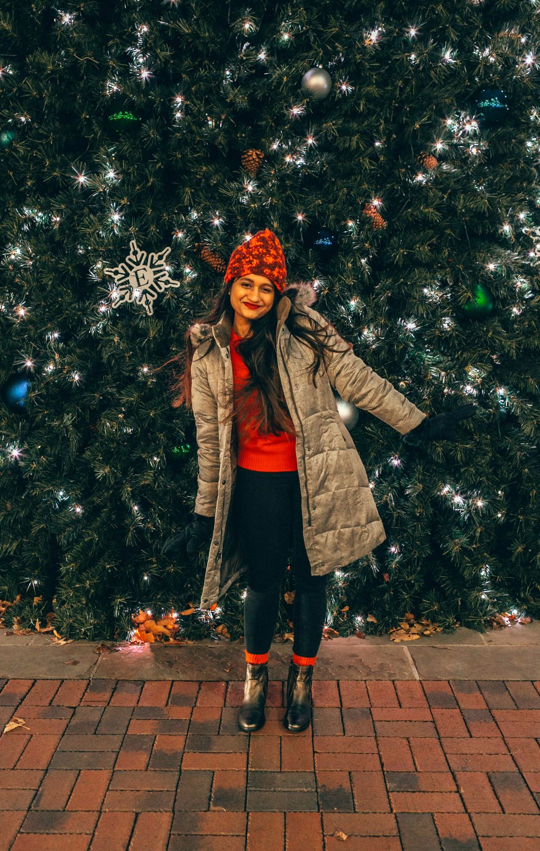 wearing Aetrex Kaitlyn metallic boots Eddie Bauer puffer jacket for Winter featured by top Ohio fashion blogger, Dreaming Loud: image of a woman in front of a Christmas tree, wearing an Eddie Bauer puffer jacket, Eddie Bauer women's gloves, Eddie Bauer red beanie, J.Crew red sweater, Aetrex metallic booties, thermal winter socks and Madewell high rise skinny jeans