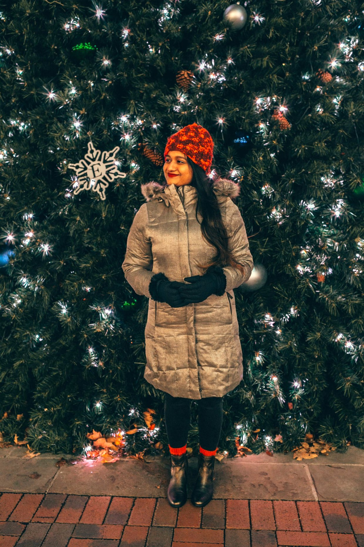 wearing Eddie Bauer Lodge Down Parka in goldEddie Bauer puffer jacket for Winter featured by top US fashion blogger, Dreaming Loud: image of a woman in front of a Christmas tree, wearing an Eddie Bauer puffer jacket, Eddie Bauer women's gloves, Eddie Bauer red beanie, J.Crew red sweater, Aetrex metallic booties, thermal winter socks and Madewell high rise skinny jeans