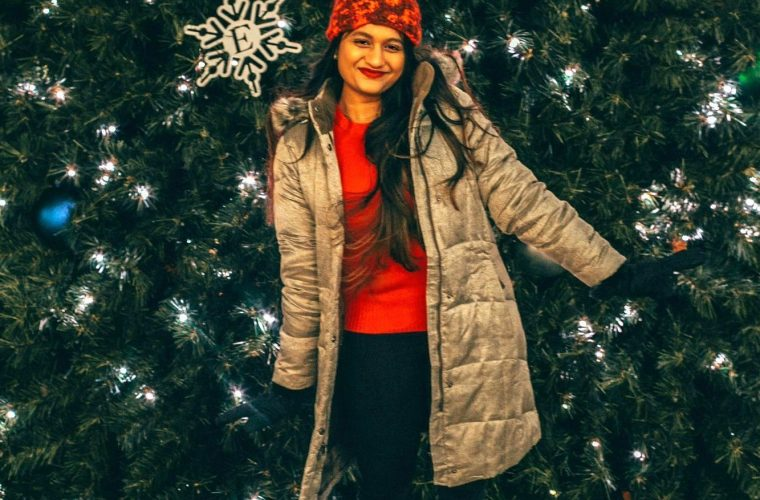 wearing Eddie Bauer ODGE DOWN PARKA in gold dustEddie Bauer puffer jacket for Winter featured by top Ohio fashion blogger, Dreaming Loud: image of a woman in front of a Christmas tree, wearing an Eddie Bauer puffer jacket, Eddie Bauer women's gloves, Eddie Bauer red beanie, J.Crew red sweater, Aetrex metallic booties, thermal winter socks and Madewell high rise skinny jeans