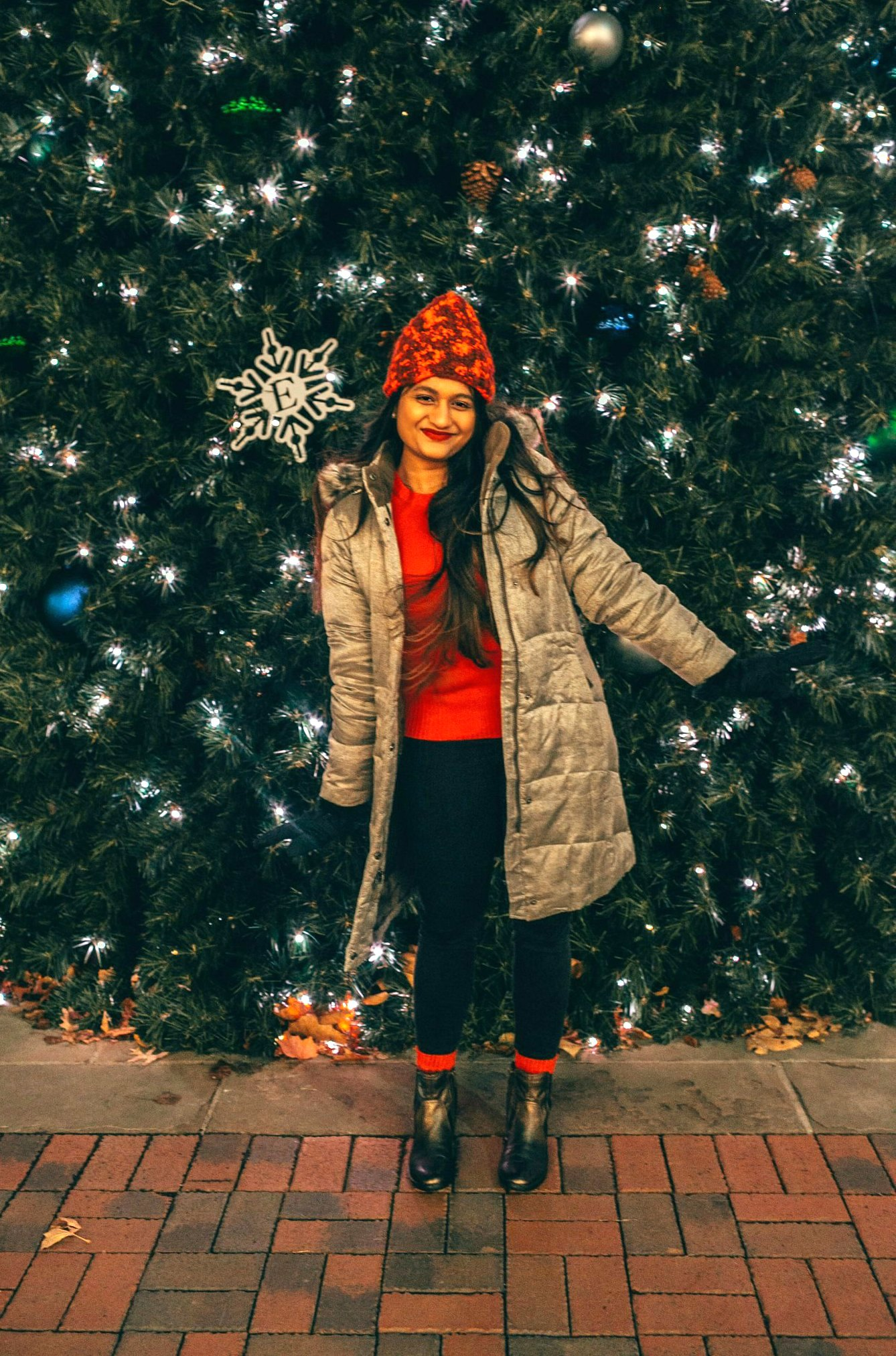 wearing Eddie Bauer ODGE DOWN PARKA in gold dustEddie Bauer puffer jacket for Winter featured by top US fashion blogger, Dreaming Loud: image of a woman in front of a Christmas tree, wearing an Eddie Bauer puffer jacket, Eddie Bauer women's gloves, Eddie Bauer red beanie, J.Crew red sweater, Aetrex metallic booties, thermal winter socks and Madewell high rise skinny jeans