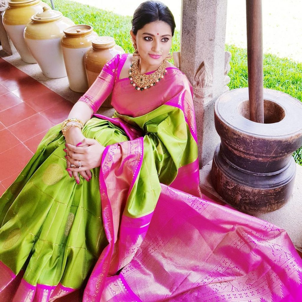 Actress Sneha wearing green Kanjeevaram saree | South Indian wedding saree trends featured by top US and Indian fashion blog, Dreaming Loud: image of a green saree