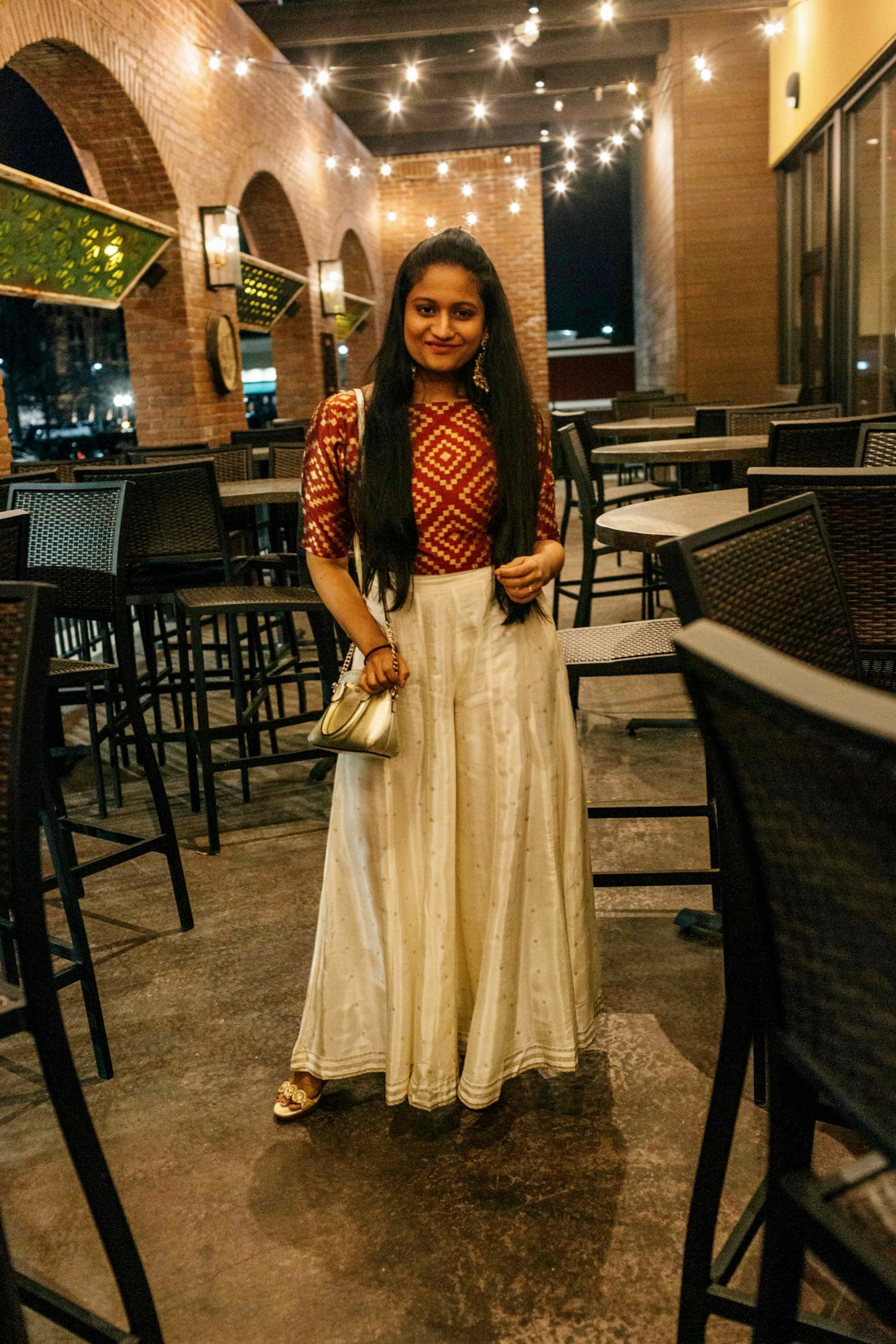 How to wear sharara palazzo pants | Indo Western Outfit for your birthday, featured by top US modest fashion blog, Dreaming Loud: image of a woman wearing a check design spree, off white silk palazzo pants, Indian statement earrings, Jack Rogers wedge sandals and a metallic chain purse
