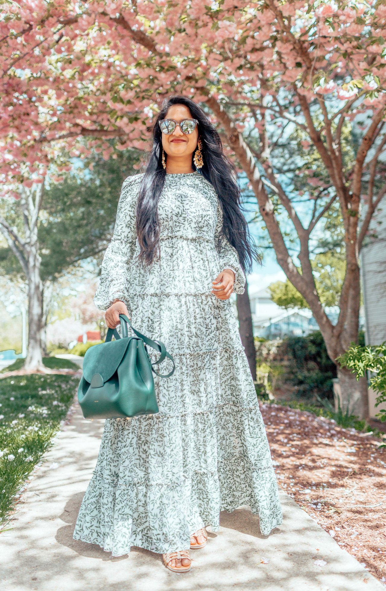 Modest Summer Wedding Guest Dresses featured by top US modest fashion blog, Dreaming Loud: image of a woman wearing a Dainty Jewel floral maxi dress, Polene numero un bag, Dolce Vita golden sandals, Indian statement earrings, Le Specs sunglasses, and a Daniel Wellington watch.