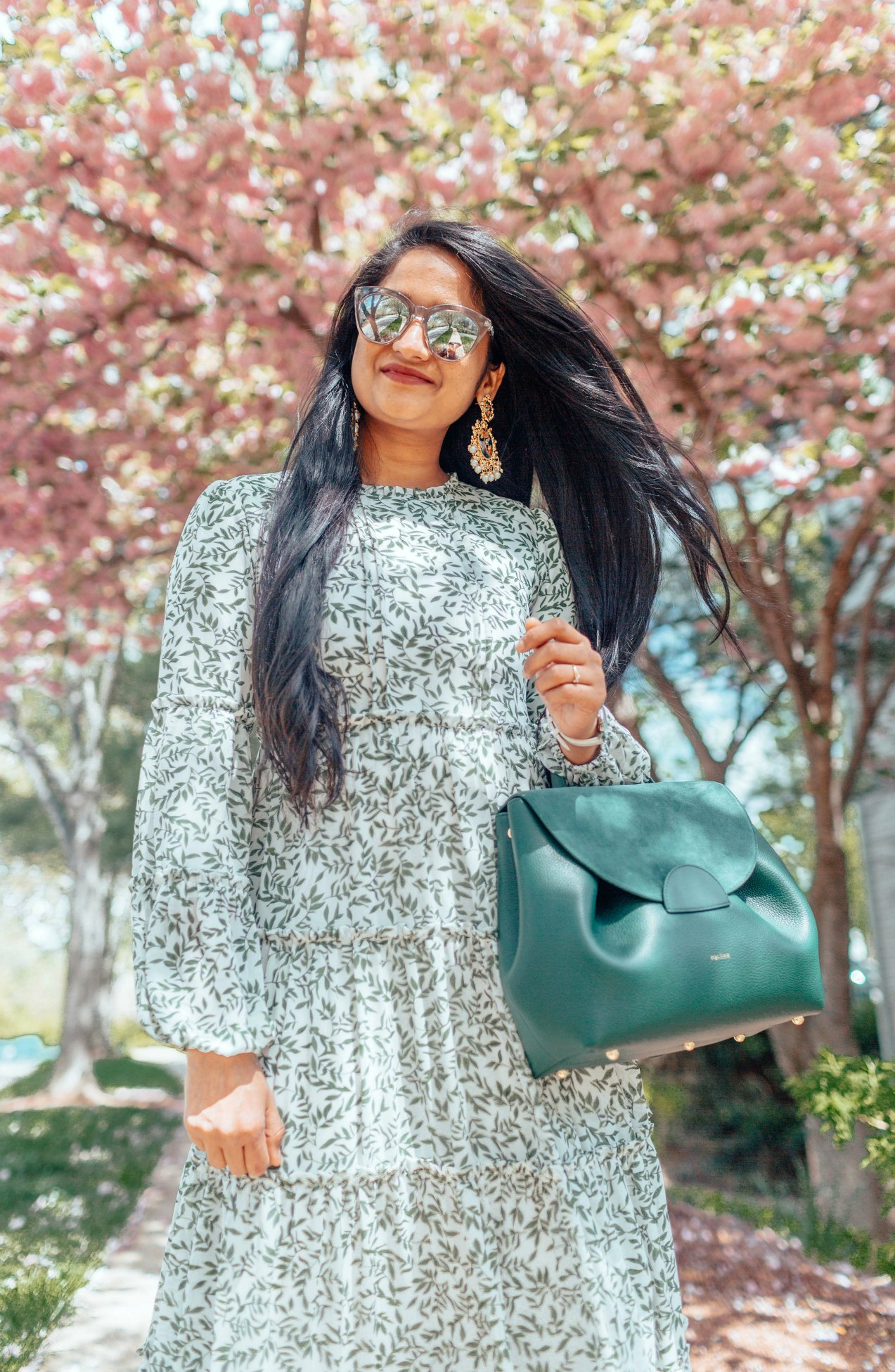 The Perfect Floral Maxi Dress for Spring featured by top US modest fashion blog, Dreaming Loud: image of a woman wearing a Dainty Jewells floral maxi dress, Polene green handbag, Dolce Vita block heel sandals, Indian statement earrings, Le Specs sunglasses and a Daniel Wellington watch