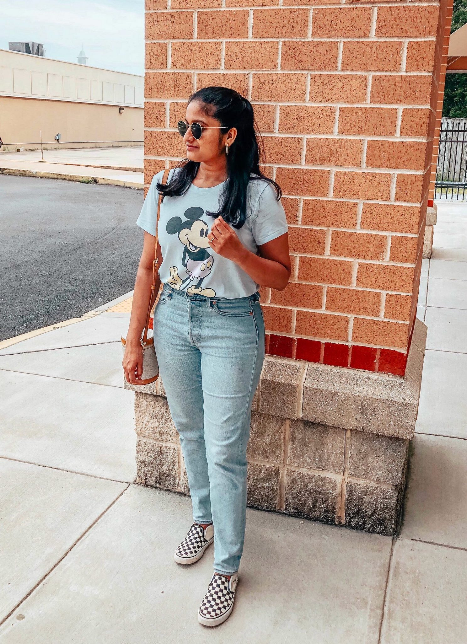 Levis high waisted crop jeans styled by top US modest blog, Dreaming Loud: image of a woman wearing a Target Mickey Mouse shirt, Levis high waisted jeans, Paravel crossbody bag, Madewell hoop earrings,  and Ray Ban round sunglasses