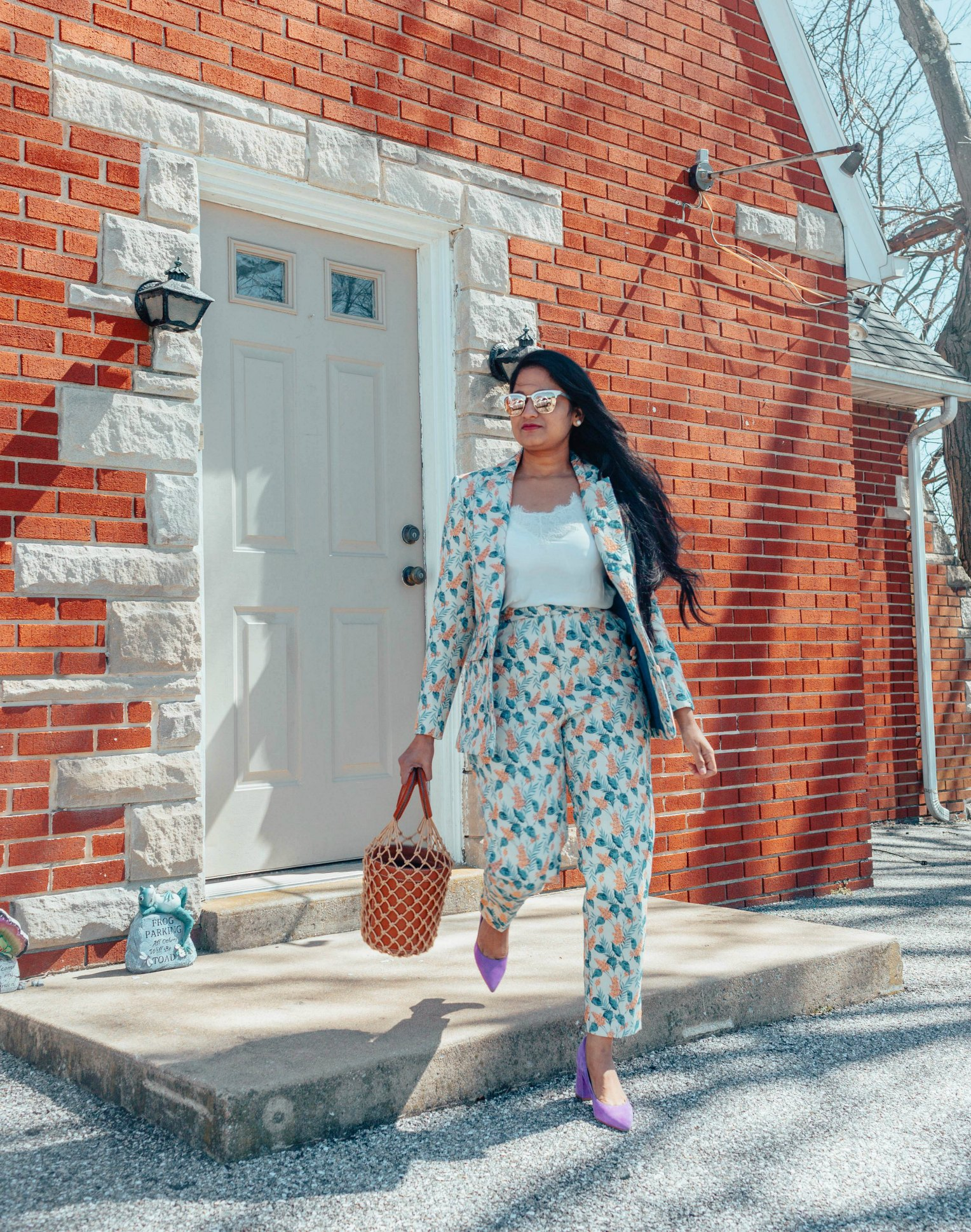 Wearing STAUD Moreau Bag | Modest Spring outfits featured by top US fashion blog, Dreaming Loud: image of a woman wearing an ASOS floral pant suit, Abercrombie and Fitch lace cami, STAUD bag, Marc Fisher pumps and Ray ban aviator sunglasses