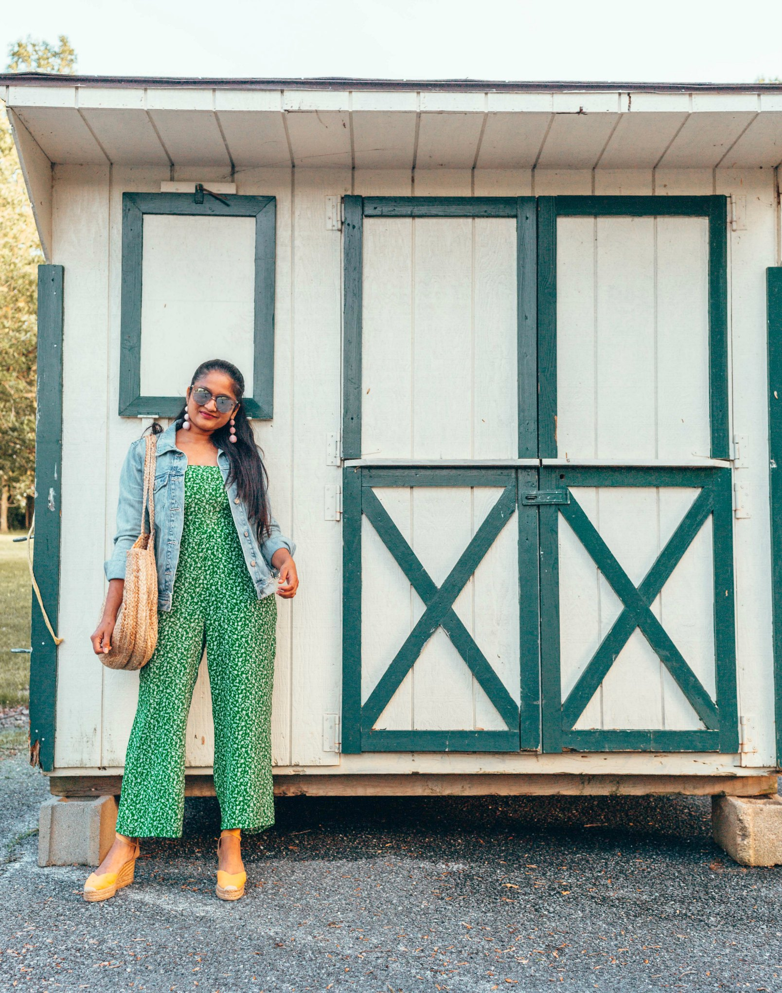 Green Floral Jumpsuit featured by top US modest fashion blog Dreaming Loud; Image of a woman wearing a Red Dress Boutique jumpsuit, Old Navy denim jacket and Castaner wedges.