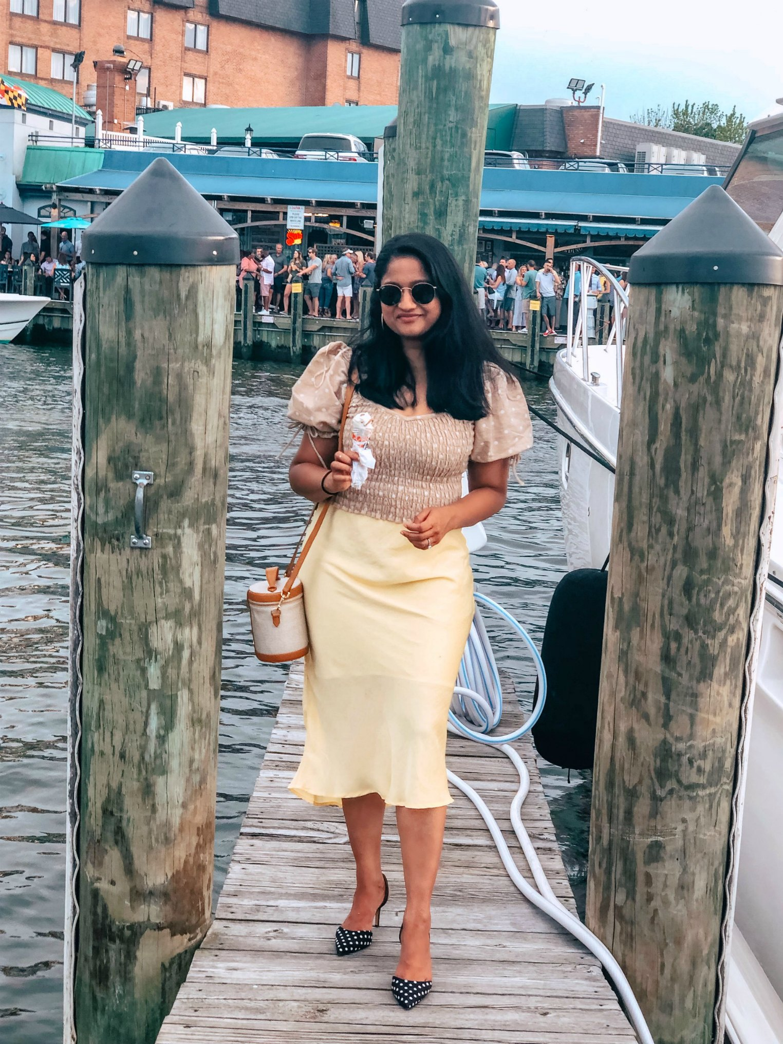 Top US modest fashion blog, Dreaming Loud, features their thoughts on Clothing Size: image of a woman wearing a Leith stain skirt, a polka dot smocked top, Ann Taylor polka dot pumps, Paravel crossbody bag, and Madewell hoop earrings.