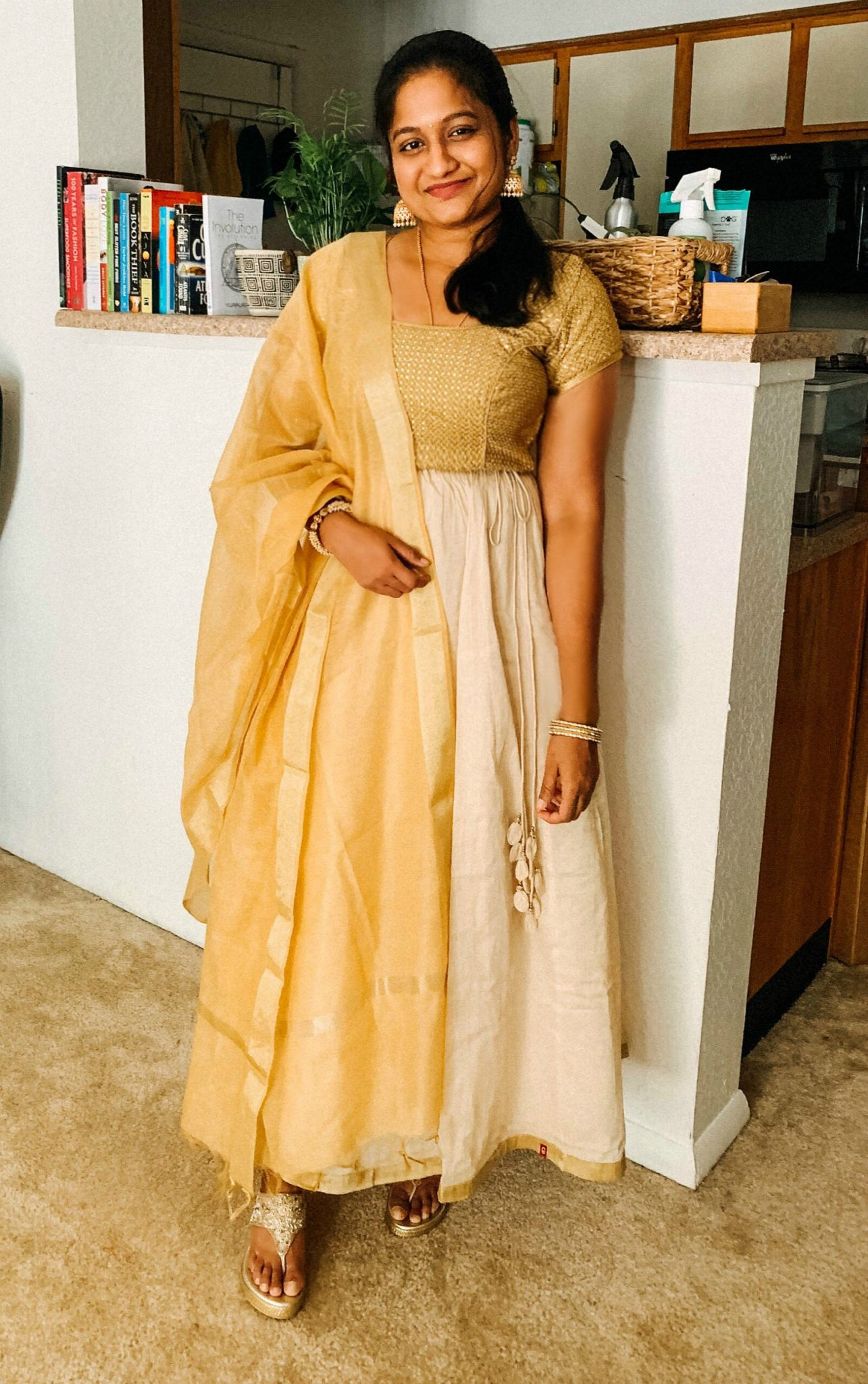 Traditional Indian gold blouse and skirt look featured by top US modest fashion blog, Dreaming Loud: image of a woman wearing a gold spree blouse, gold silk skirt, gold dupatta, Indian traditional earrings, Crimzon golden wedges, Gold bindi and a Paravel crossbody bag,