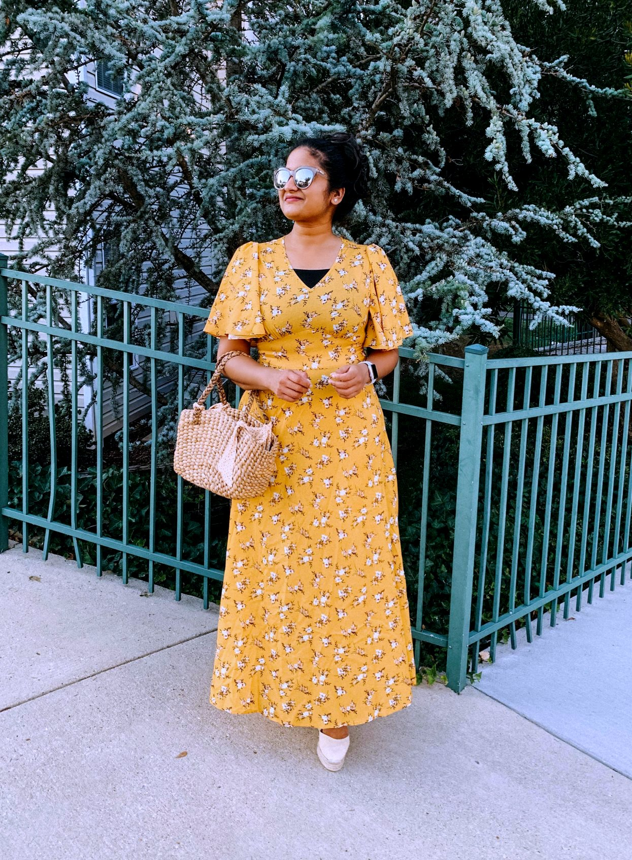 SheIn Floral Flutter Sleeve Dress Under $20 styled by top US modest fashion blog, Dreaming Loud: image of a woman wearing a SheIn Flora flutter sleeve dress, Castaner wedge espadrilles, American Eagle bralette, wicker straw tote from Amazon, Le Specs sunglasses.