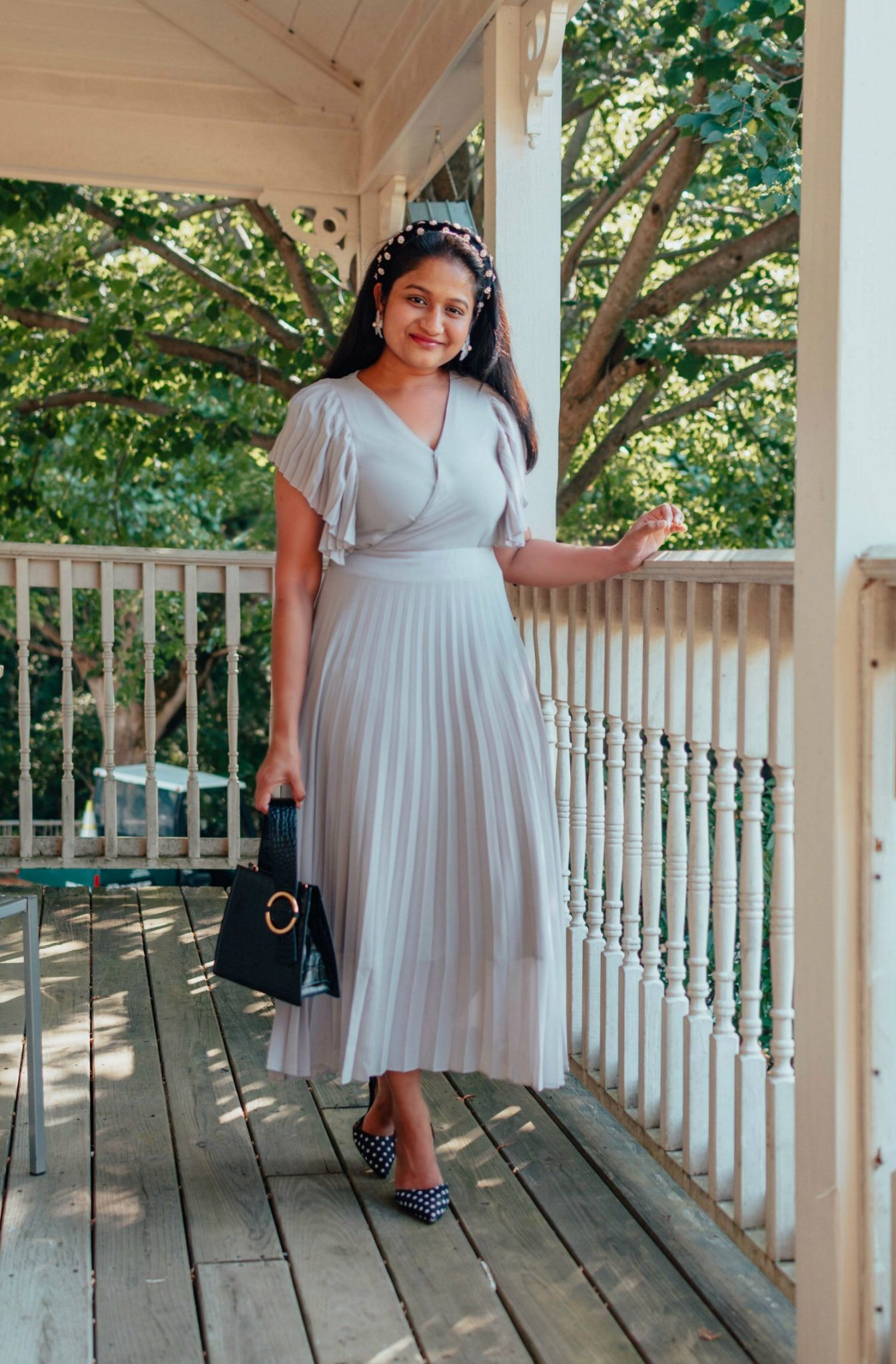 Modest Summer Wedding Guest Dresses featured by top US modest fashion blog, Dreaming Loud: image of a woman wearing an Ivy City Co dress, Baublebar flower earrings, Ann Taylor polka dot pumps, black velvet jeweled headband, Parisa Wang handle bag.