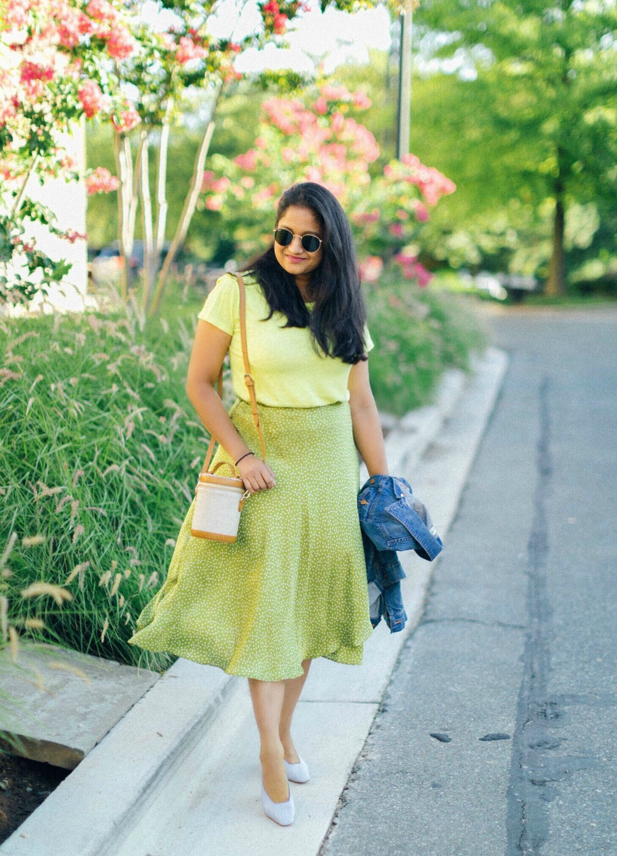 wearing Mango Polka dots satin midi skirt , B.P. Tee, Paravel Capsule bag, light blue heels | Best Labor Day Sales-Women's Clothing & Fashion by popular fashion blog, Dreaming Loud: image of a woman standing under a tall flowering bush and wearing  Mango Polka dots satin midi skirt, B.P. Tee, Capsule bag, and light blue heels.