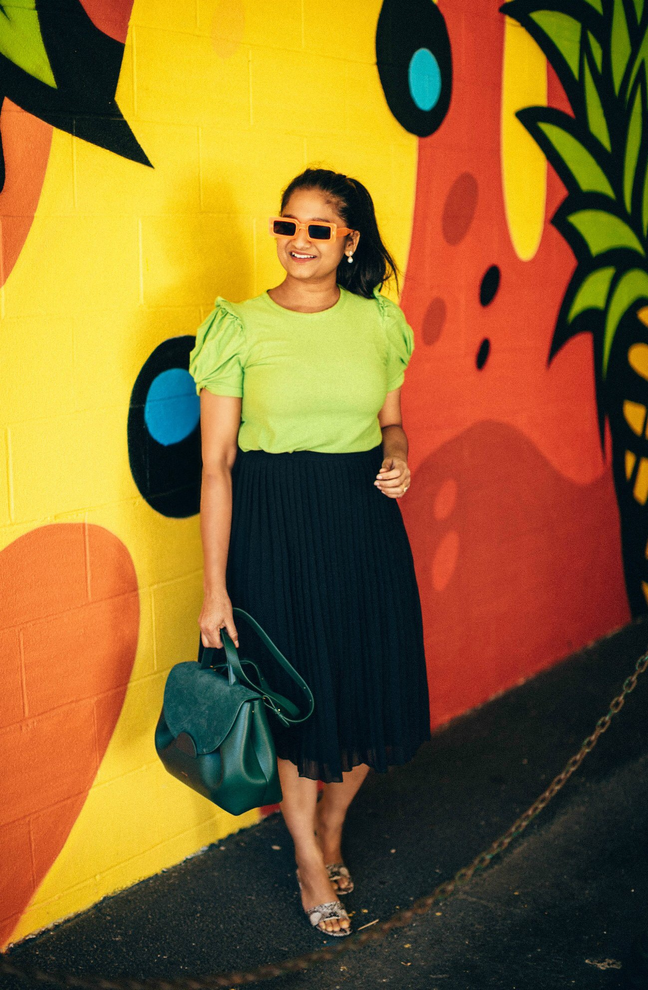 How to Take your Workwear Pieces from Day to Night featured by top US modest fashion blog, Dreaming Loud: image of a woman wearing black pleated skirt,MOON RIVER Women's Ruched Tee, snake print shoes, polene numero uno bag