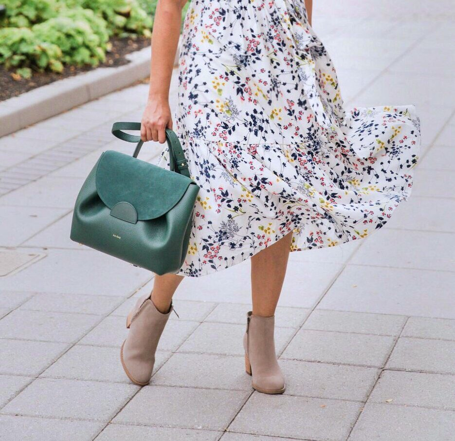 Early fall fashion look featured by top US modest fashion blog, Dreaming Loud: image of a woman wearing a Modest Passion Collection floral midi dress, Polene handbag, Brooks Brothers trench coat, Blonde suede boots, and Baublebar heart drop earrings.