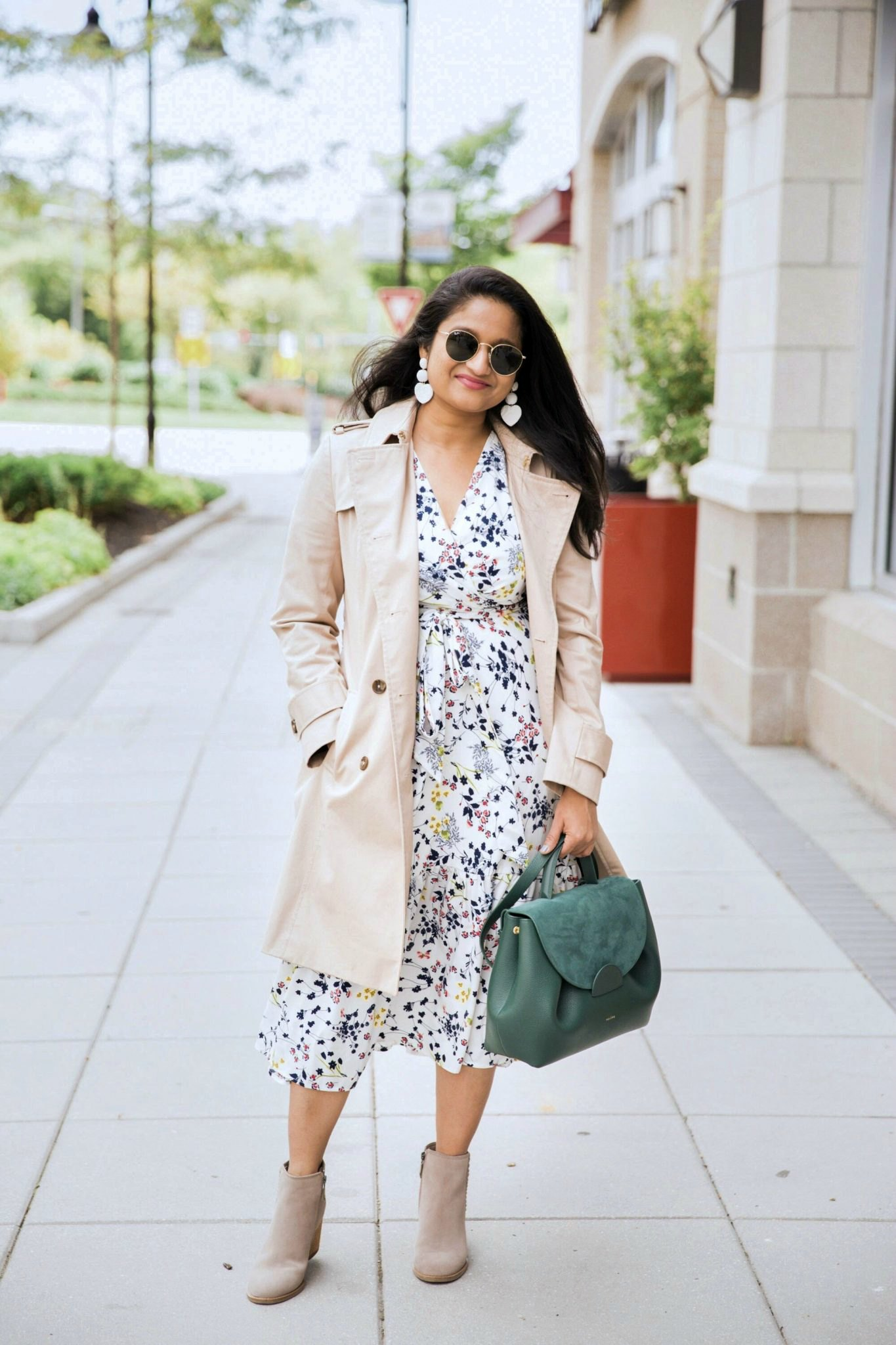 Early fall fashion look featured by top US modest fashion blog, Dreaming Loud: image of a woman wearing a Modest Passion Collection floral midi dress, Polene handbag, Brooks Brothers trench coat, Blonde suede boots, and Baublebar heart drop earrings | Lightweight Jackets by popular Maryland modest fashion blog, Dreaming Loud: image of a woman wearing white and blue floral print dress, tan jacket, tan ankle boots, white statement earrings, and holding green purse.