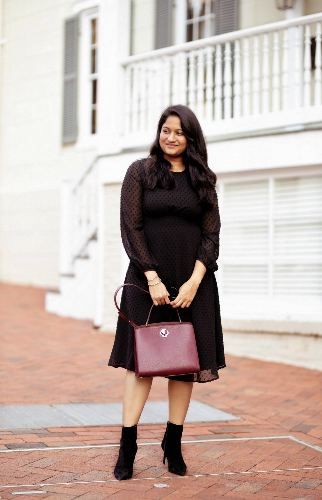 wearing skirt society Althea Black Swissdot Dress, brooks brother trench coat, banana republic Althea Black Swissdot Dress, Kate spade omy medium satchel | The Perfect Little Black Dress You Need for Every Occasion and it's Under $50 by popular modest fashion blog, Dreaming Loud: image of a woman outside wearing a Skirt Society Althea Black Swissdot Dress, Bauble Bar MINI AMARIELLA FLOWER STUD RESIN EARRINGS, Gap Skinny-Heel Ankle Boot, and holding a romy medium satchel.