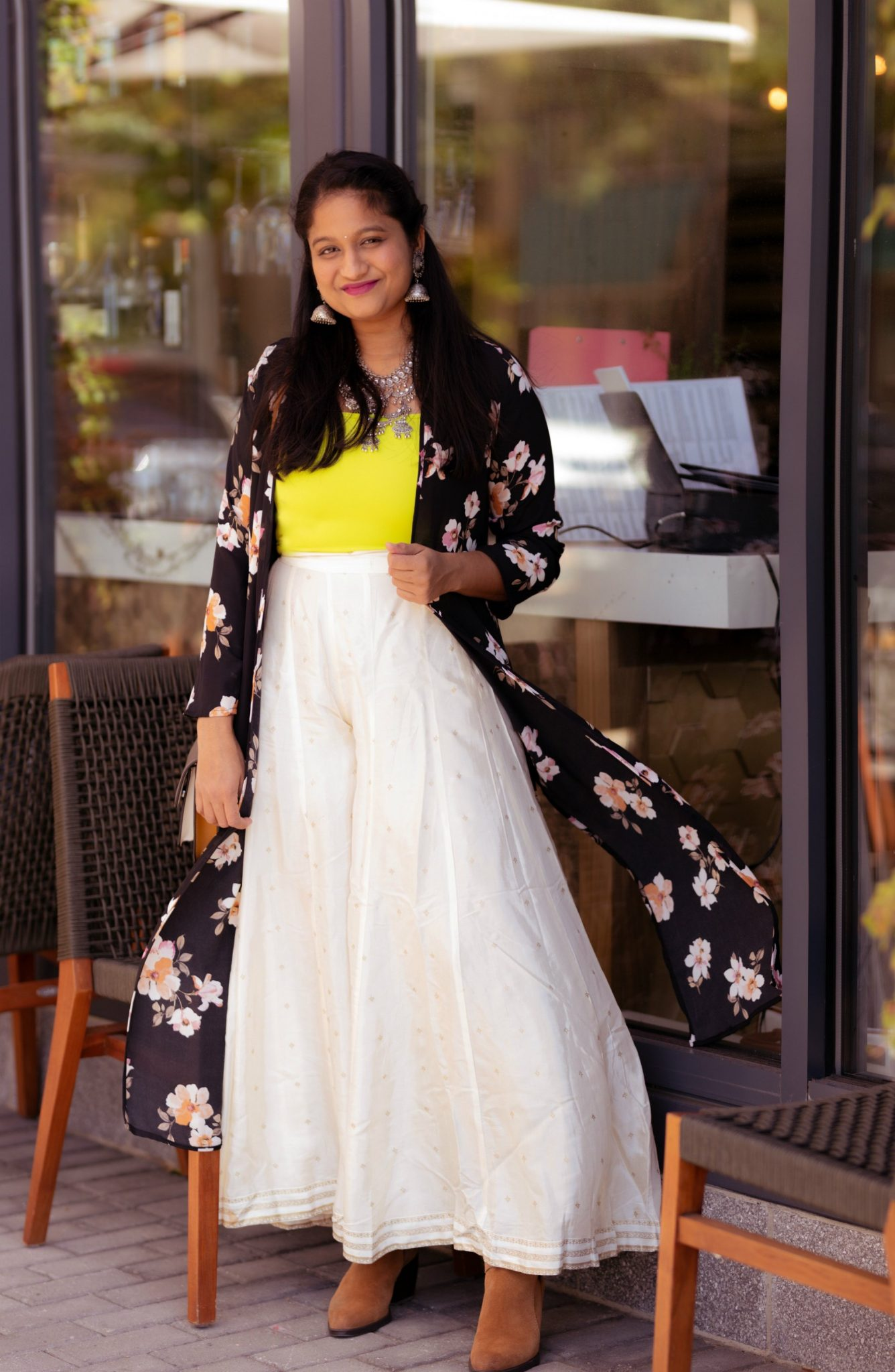 5-Cute-Diwali-Outfits-to-Wear-for-your-Diwali-Party-Neon-crop-top-silver-Afghani-statement-necklaceoff-white-palazzo-pantsfloral-kimono-Naturalizer-Fenya-Booties | Lightweight Jackets by popular Maryland modest fashion blog, Dreaming Loud: image of a woman wearing a black floral print chiffon kimono, neon yellow top, brown suede ankle boots, and white eyelet skirt.
