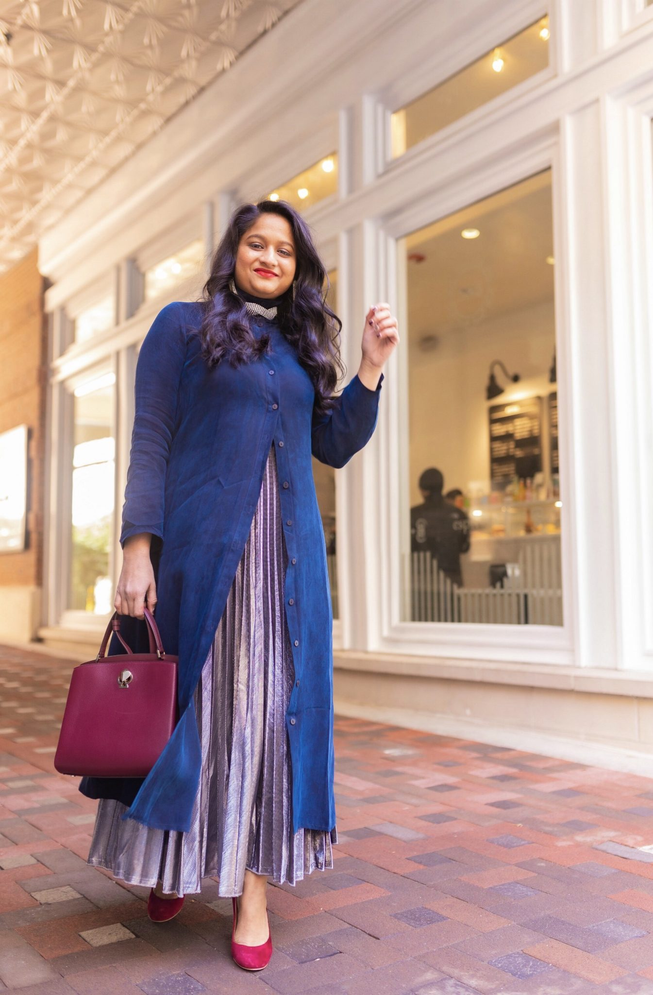 Pongal festival outfits or Makara Sankranthi featured by top US Indian fashion blog, Dreaming Loud: image of a woman wearing The froknyc Iconic Dress in navy, Silver pleated skirt, kate spade Ro mySatchel Bag 10