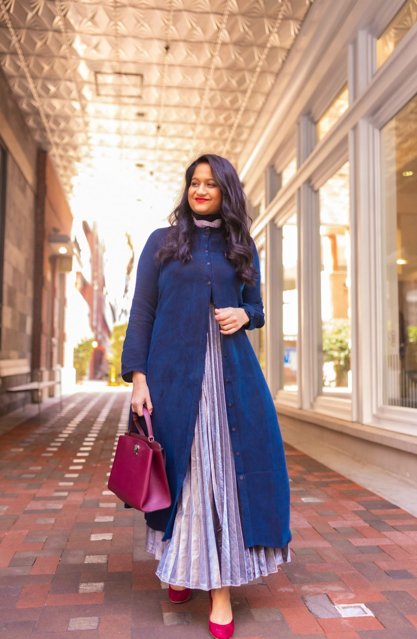 Pongal festival outfits or Makara Sankranthi featured by top US Indian fashion blog, Dreaming Loud: image of a woman wearing The froknyc Iconic Dress in navy, Silver pleated skirt, kate spade Ro mySatchel Bag 11