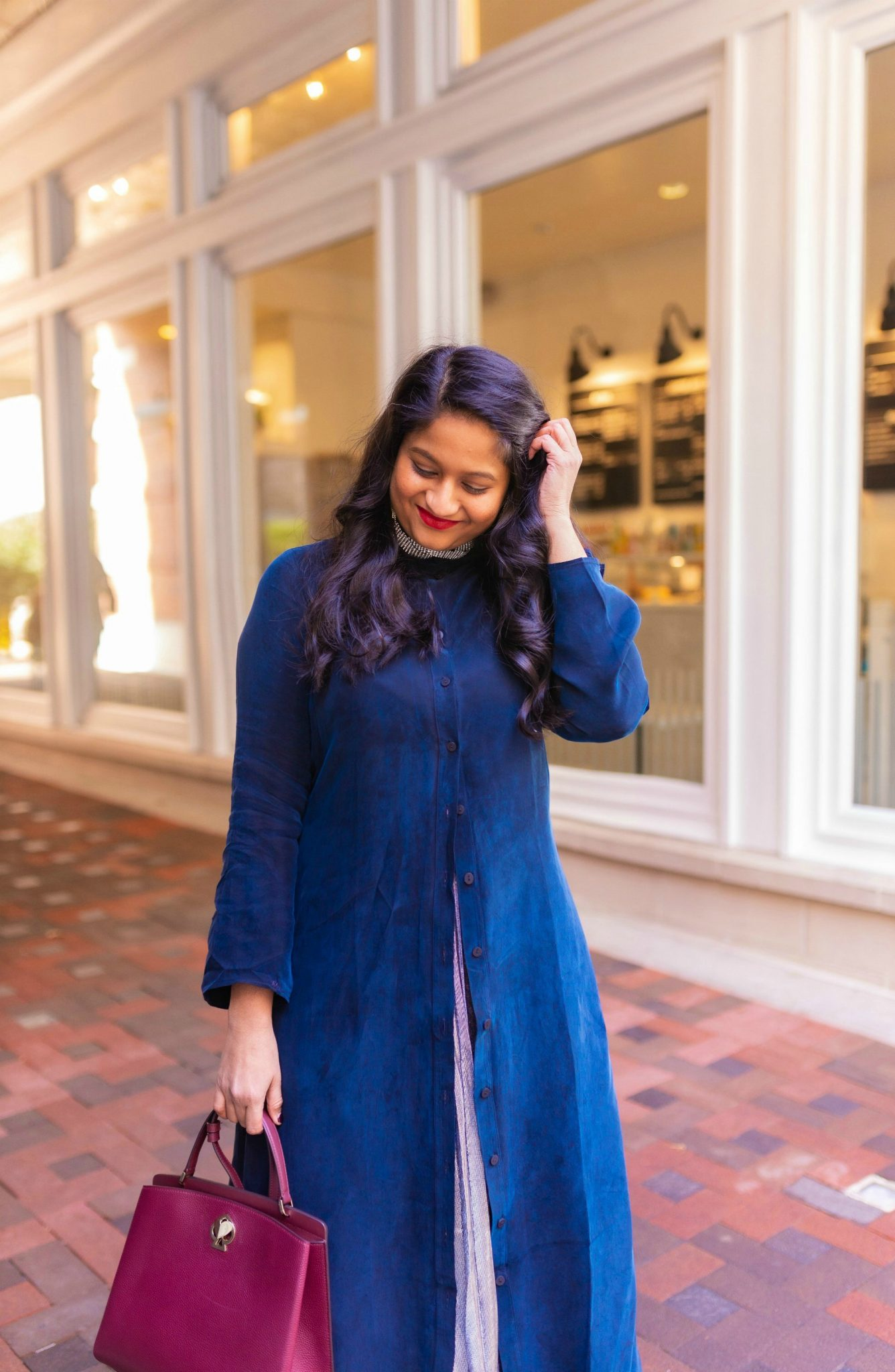 Pongal festival outfits or Makara Sankranthi featured by top US Indian fashion blog, Dreaming Loud: image of a woman wearing The froknyc Iconic Dress in navy, Silver pleated skirt, kate spade Ro mySatchel Bag 6