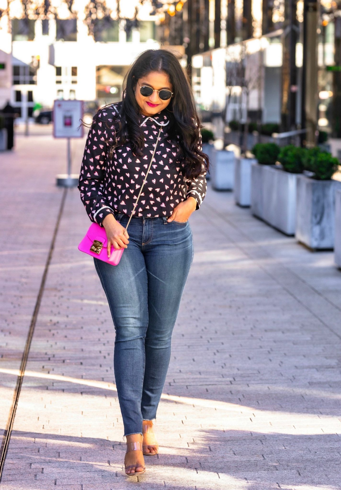 Allegra K Heart Print Blouse styled for for Valentine's Day by top US modest fashion blog, Dreaming Loud: image of a woman Wearing Allegra k Heart print blouse, Ag Farrah Ankle jeans, Banana Republic hot pink coat, schutz Ariella Heeled Transparent Sandal, Furla Metropolis bag
