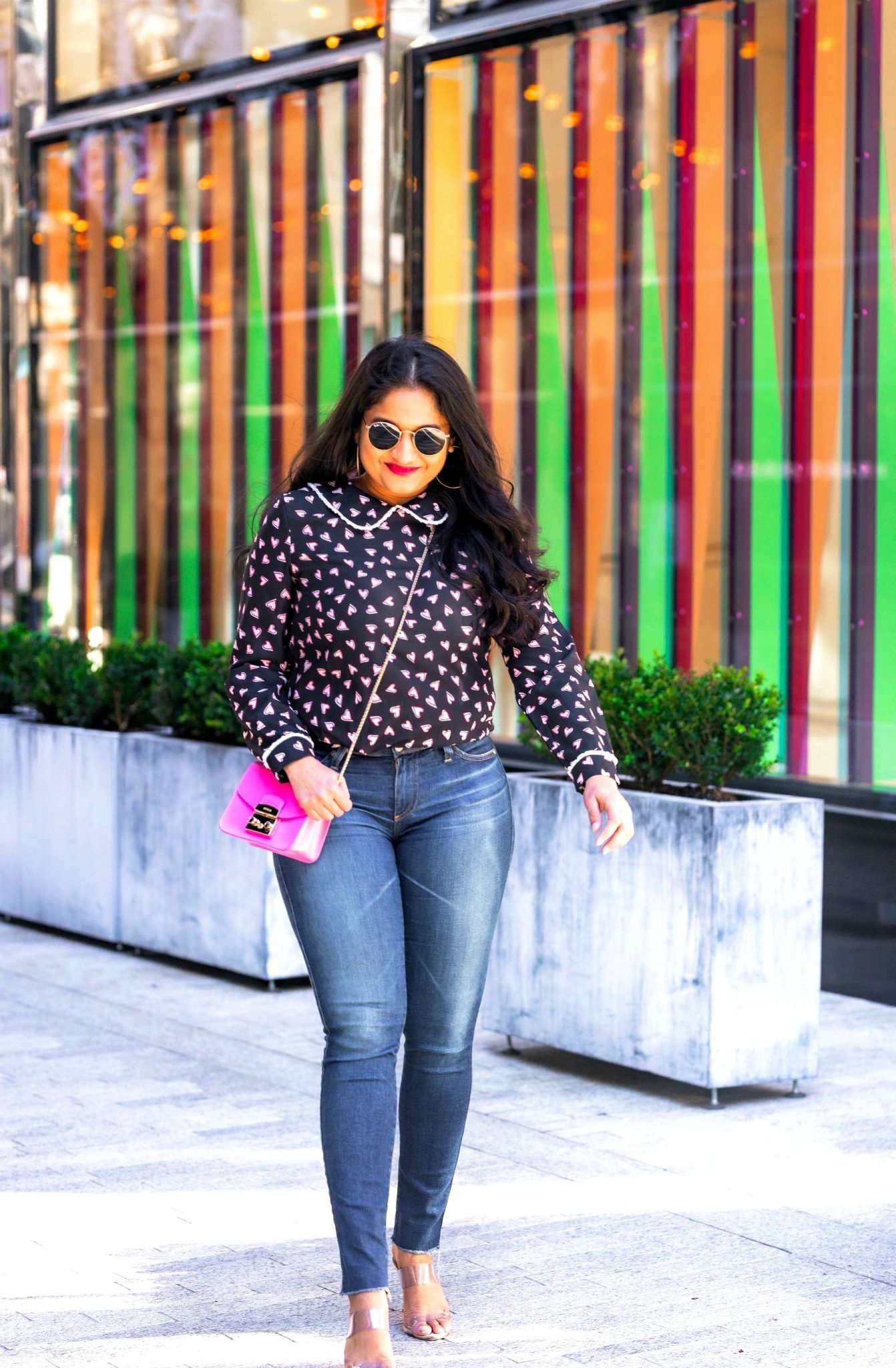 Allegra K Heart Print Blouse styled for for Valentine's Day by top US modest fashion blog, Dreaming Loud: image of a woman Wearing Allegra k Heart print blouse_ Ag Farrah Ankle jeans_ Banana Republic hot pink coat_ schutz Ariella Heeled Transparent sandals