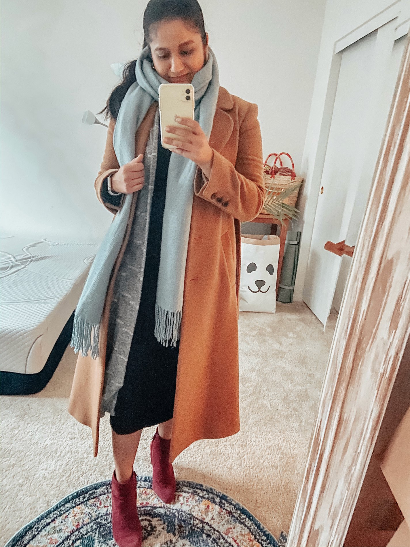 Camel Coat Outfits for Work styled by top US modest fashion blog, Dreaming Loud: image of a woman Wearing black ribbed midi dres, long cardigan, light blue scarf, &other stories A-line camel coat, Banana republic skinny heel ankles boots in burgundy
