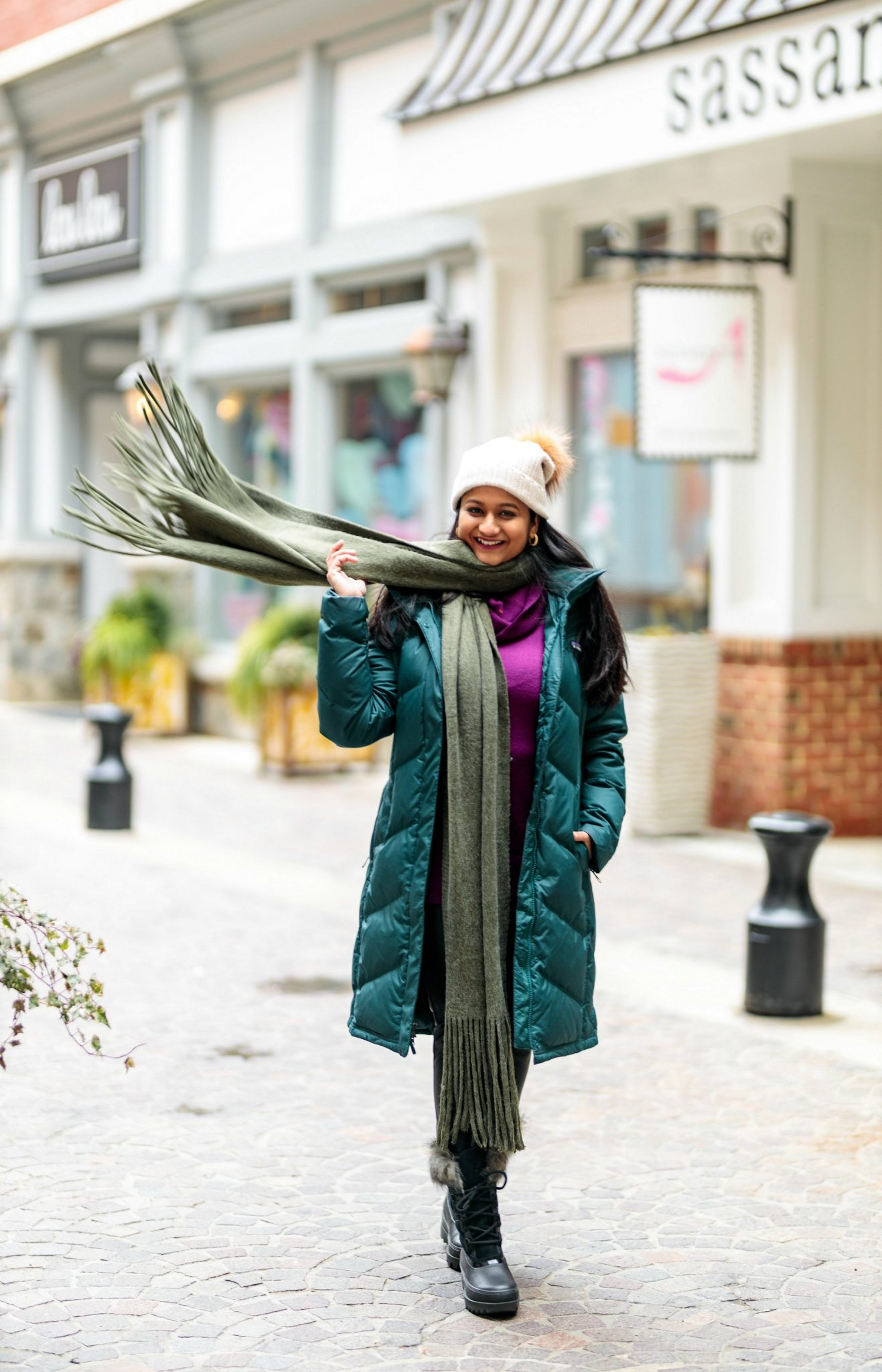 My favorite Winter Outfit with Patagonia Down Parka and Sorel Next Snow Boots featured by top US fashion blog, Dreaming Loud. photo of a women Wearing PATAGONIA Down With It Hooded Down Parka, Sorel Joan of Arctic snow boots, Free people scarf, faux leather legging, pom beanie