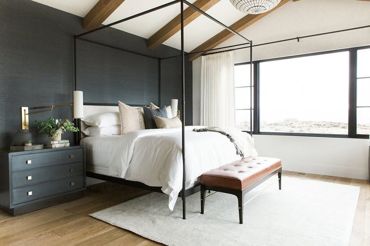 12 Dark Bedroom Ideas for a Cozy and Dramatic Look featured by top US lifestyle blog, Dreaming Loud: Master bedroom+in+blue+grasscloth+wallpaper,+statement+chandelier,+and+leather+bench (1) | Dark Bedroom Ideas by popular Michigan lifestyle blog, Dreaming Loud: image of a bedroom with dark grass cloth wallpaper.