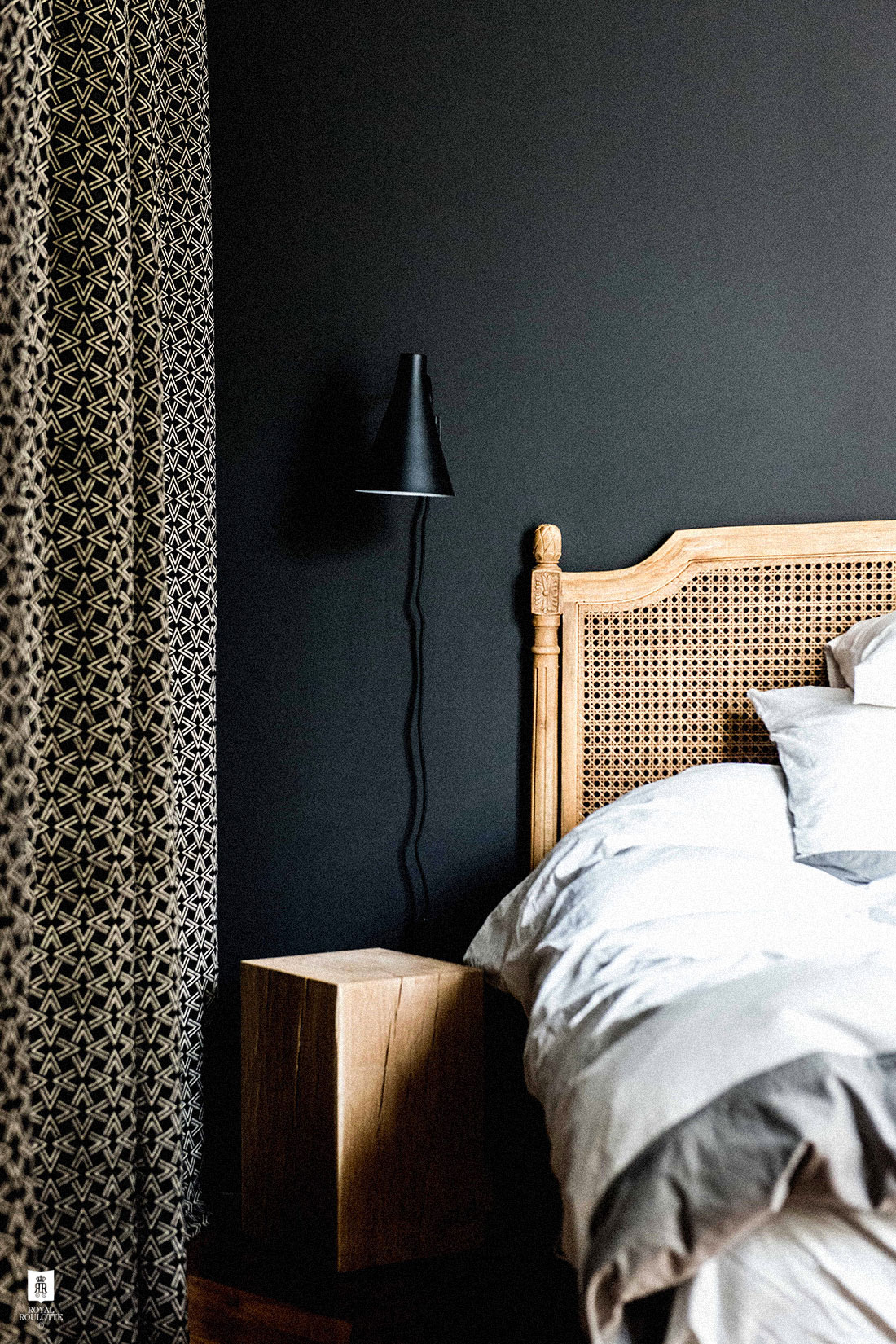12 Dark Bedroom Ideas for a Cozy and Dramatic Look featured by top US lifestyle blog, Dreaming Loud: black bedroom with cane bed frame | Dark Bedroom Ideas by popular Michigan lifestyle blog, Dreaming Loud: image of a bedroom with black walls and a cane bed frame.