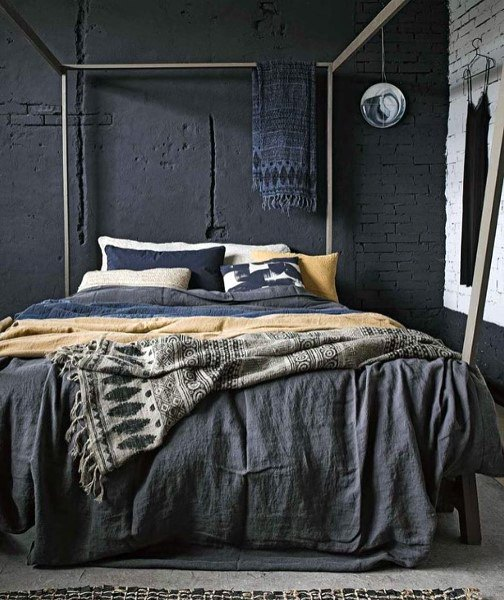 12 Dark Bedroom Ideas for a Cozy and Dramatic Look featured by top US lifestyle blog, Dreaming Loud: brick-wall-black-bedrooms | Dark Bedroom Ideas by popular Michigan lifestyle blog, Dreaming Loud: image of a bedroom with a black and white brick wall.
