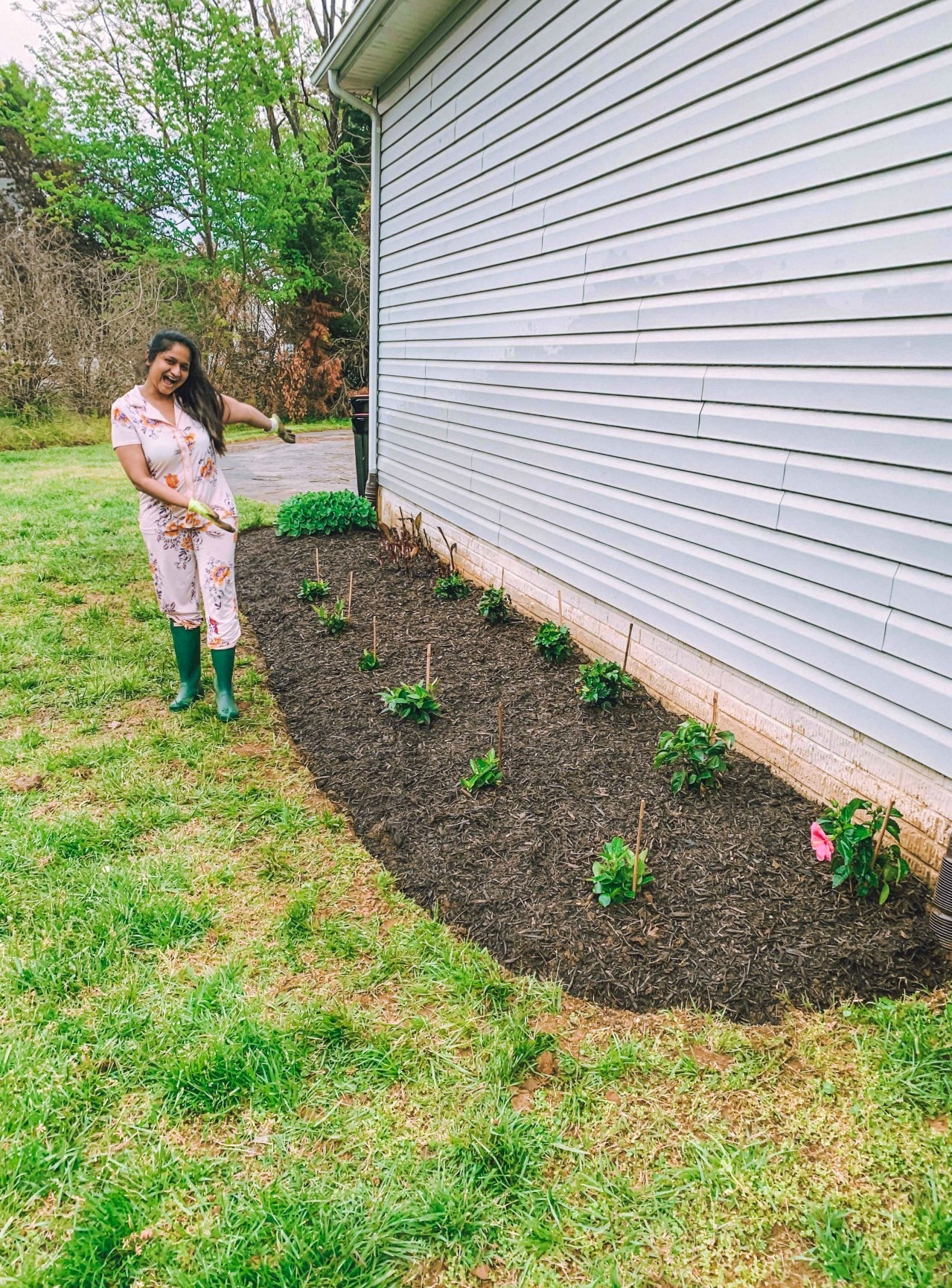 How to build ayour own flower bed.3 | Flower Bed Design by popular Michigan life and style blog, Dreaming Loud: image of a woman wearing pink floral pajamas and standing next to a flower bed on the side of her house.