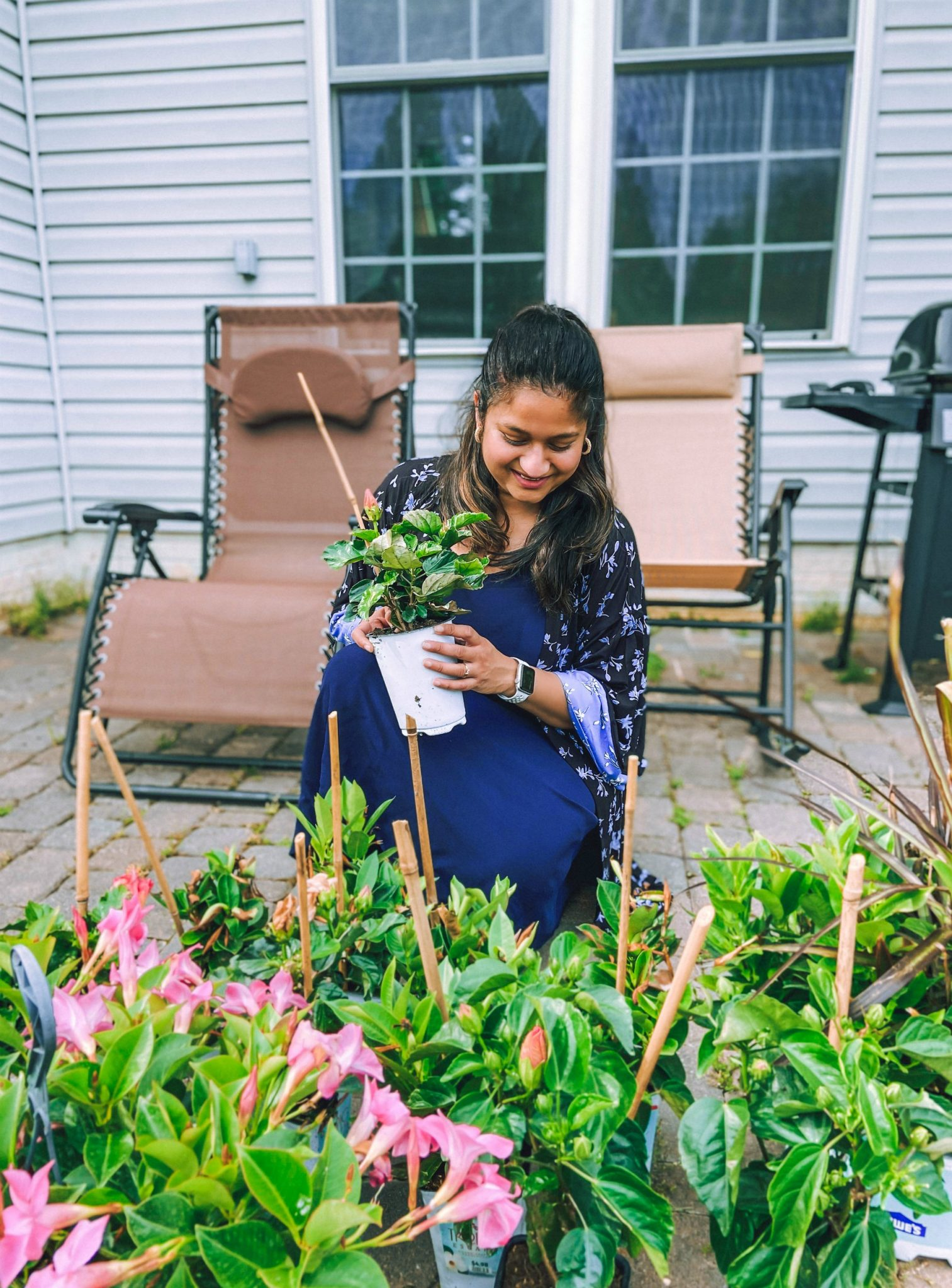 How to plant an In-ground Garden | Flower Bed Design by popular Michigan life and style blog, Dreaming Loud: image of a woman wearing a blue floral duster and blue dress and looking at some hibiscus flowers on her back patio.