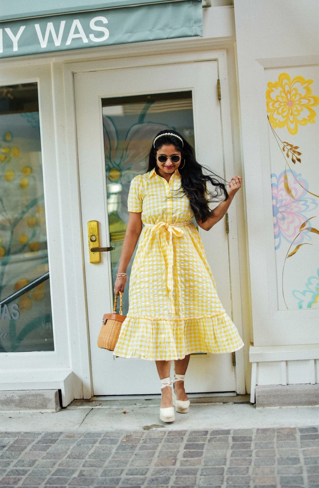 Wearing Wearing Lisa Marie Fernandez for Target Gingham Puff Sleeve Shirtdress, Castaner Carina Wedges in Cream, J.McLaughlin Ava wicker bag, pearl Headband 2 | Lisa Marie Fernandez by popular Maryland fashion blog, Dreaming Loud: image of a woman a Target Lisa Marie Fernandez yellow gingham dress, Castañer cream Carina 80 ankle tie wedge sandals, Amazon LXBSIYI Huge Gold Hoop Earrings, Olive and Piper Madison Pearl Headband, and holding a J. McLaughlin Skip to the end of the images gallery Skip to the beginning of the images gallery Ava Wicker Bag.