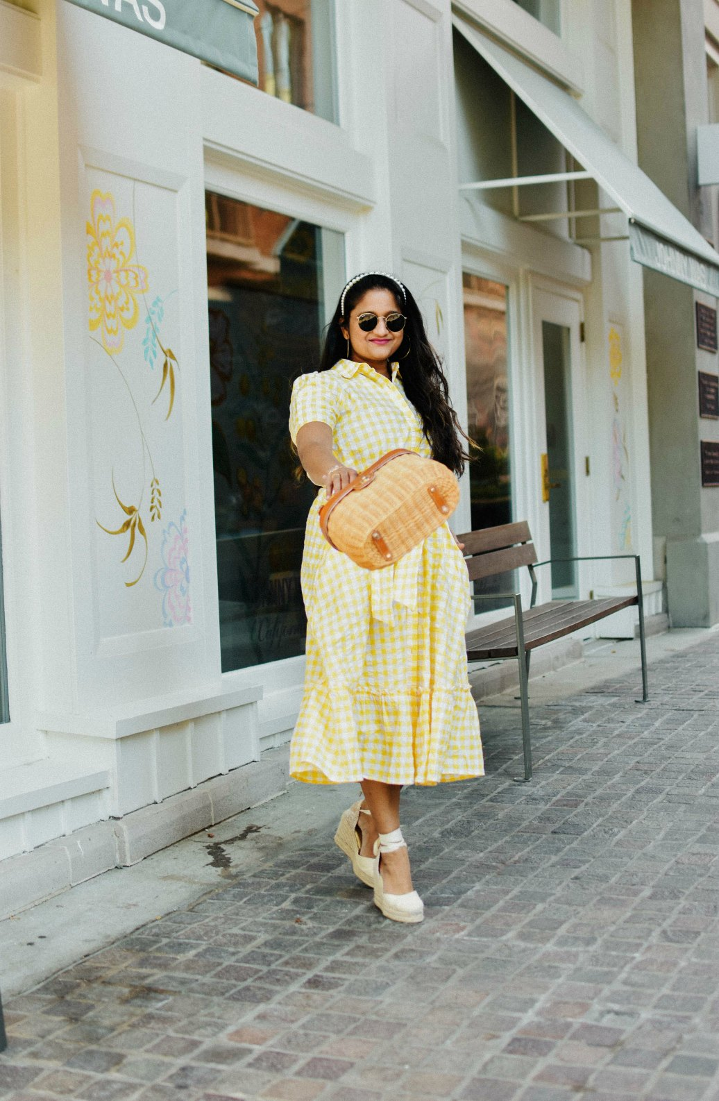 Wearing Wearing Lisa Marie Fernandez for Target Gingham Puff Sleeve Shirtdress, Castaner Carina Wedges in Cream, J.McLaughlin Ava wicker bag, pearl Headband 7 | Lisa Marie Fernandez by popular Maryland fashion blog, Dreaming Loud: image of a woman a Target Lisa Marie Fernandez yellow gingham dress, Castañer cream Carina 80 ankle tie wedge sandals, Amazon LXBSIYI Huge Gold Hoop Earrings, Olive and Piper Madison Pearl Headband, and holding a J. McLaughlin Skip to the end of the images gallery Skip to the beginning of the images gallery Ava Wicker Bag.