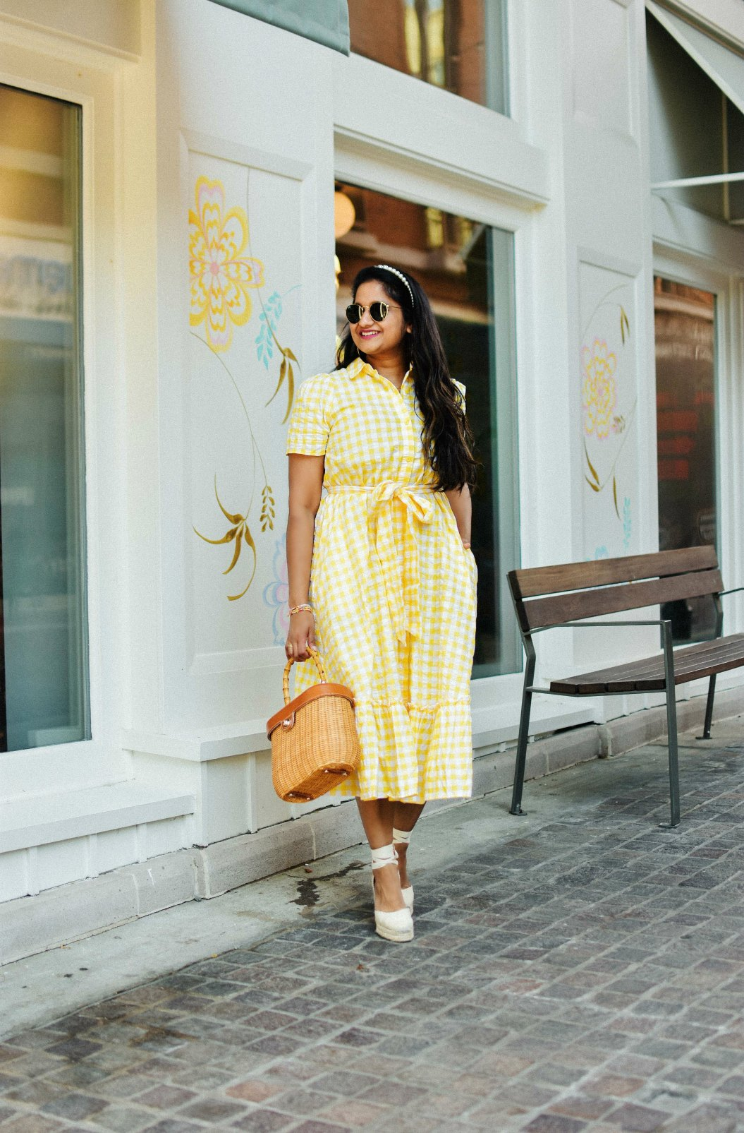 Wearing Wearing Lisa Marie Fernandez for Target Gingham Puff Sleeve Shirtdress, Castaner Carina Wedges in Cream, J.McLaughlin Ava wicker bag, pearl Headband 8  | Lisa Marie Fernandez by popular Maryland fashion blog, Dreaming Loud: image of a woman a Target Lisa Marie Fernandez yellow gingham dress, Castañer cream Carina 80 ankle tie wedge sandals, Amazon LXBSIYI Huge Gold Hoop Earrings, Olive and Piper Madison Pearl Headband, and holding a J. McLaughlin Skip to the end of the images gallery Skip to the beginning of the images gallery Ava Wicker Bag.