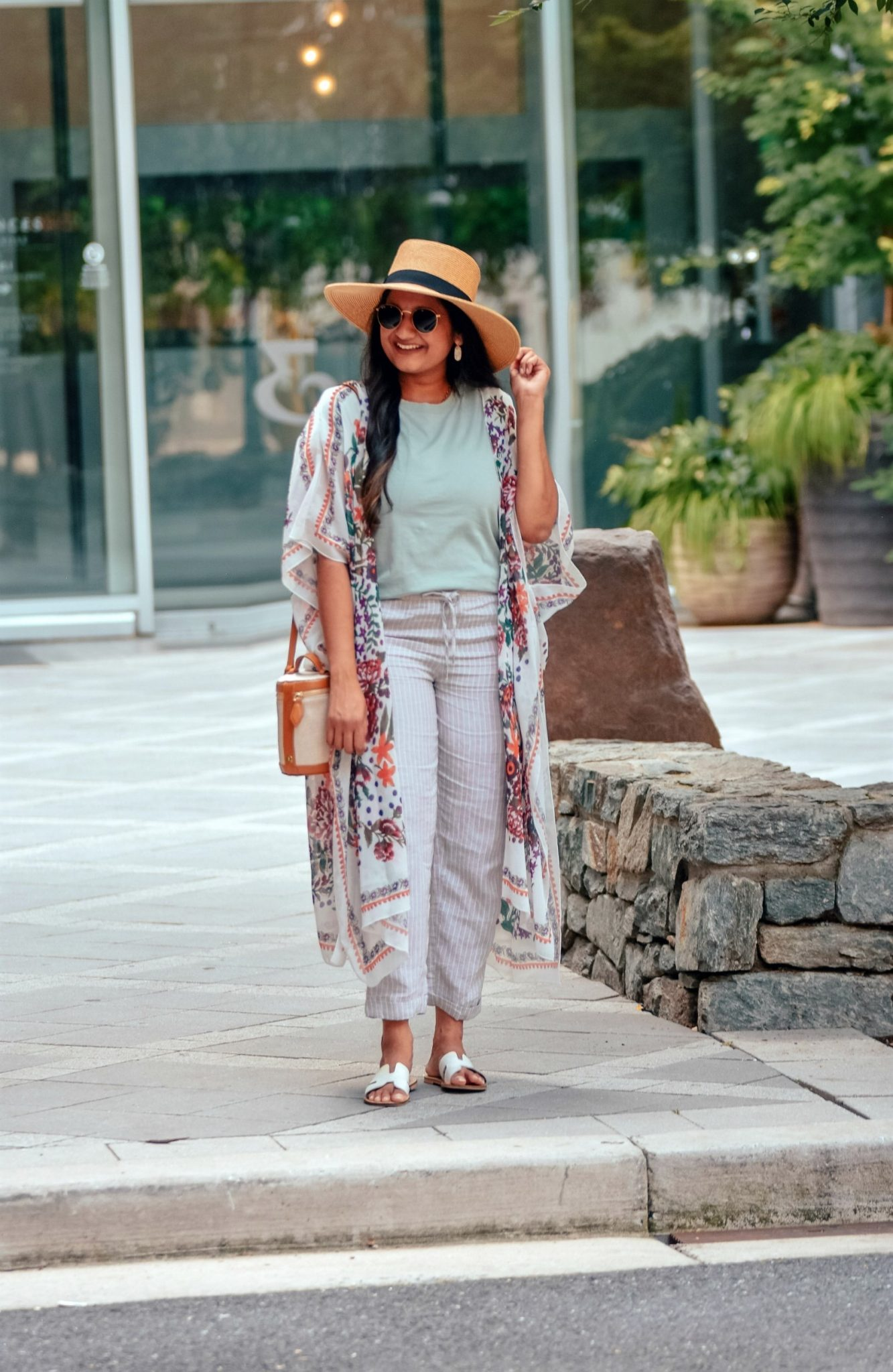 Wearing H&M Pull-on Linen Pants, Madewell Northside Vintage Tee,Hibluco Sheer Chiffon Floral Kimono,Steve Madden Greece Sandal 10 | Floral Kimono by popular Maryland fashion blog, Dreaming Loud: image of a woman walking outside by some shade umbrellas and wearing a Amazon Hibluco Women's Sheer Chiffon Floral Kimono, Madewell Northside Vintage Tee, H&M Linen Joggers, Amazon Steven Women's Greece Slides, Kendra Scott Lee Gold Drop Earrings In White Kyocera Opal, Paravel Crossbody Capsule, and Nordstrom Joanna Straw Hat BRIXTON.