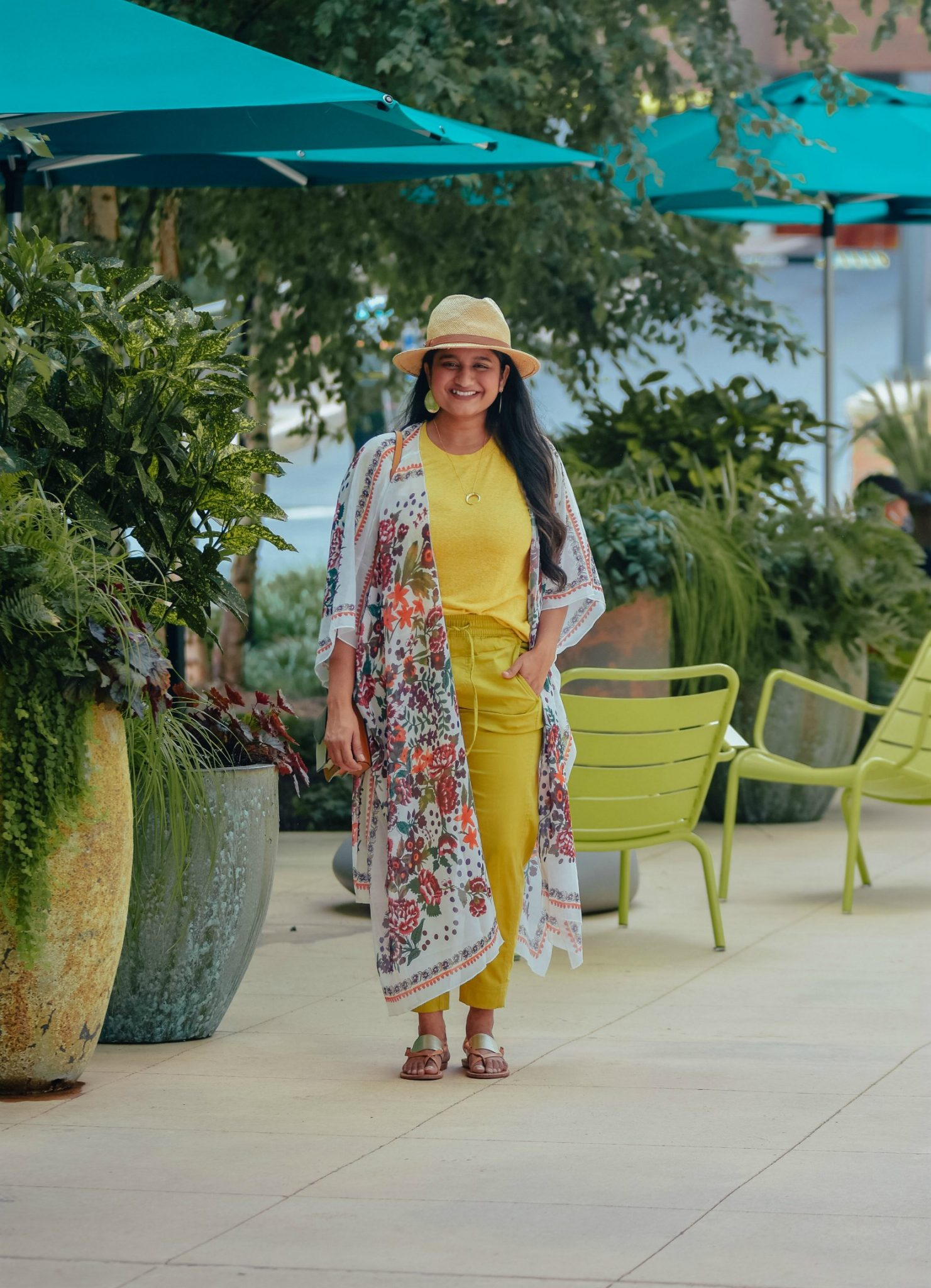 Wearing Hibluco Chiffon Floral Kimono, Madewell Whisper Cotton tee, Lou and Grey Cosmic Jogger, Soludos Metallic sandals | Floral Kimono by popular Maryland fashion blog, Dreaming Loud: image of a woman walking outside by some shade umbrellas, yellow chairs, and potted plants and wearing a Amazon Hibluco Women's Sheer Chiffon Floral Kimono, Madewell Whisper Cotton Rib-Crewneck Tee, Lou & Grey Cosmic Joggers, Amazon Soludos Women's Slotted Thong Sandals, Gorjana necklace and Shopbop Botkier Cobble Hill Crossbody Bag.