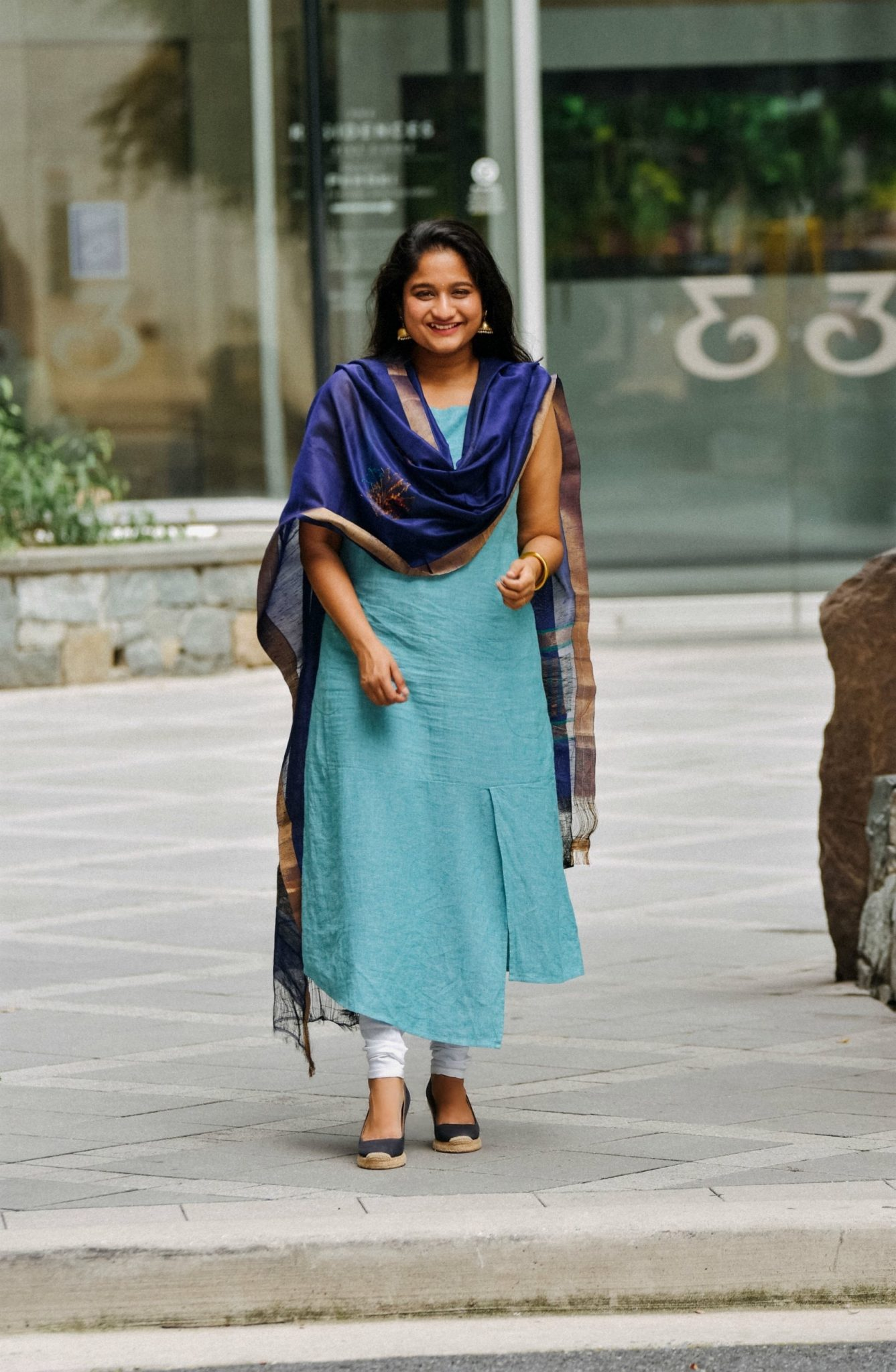 Indo-western churidar outfit-Wearing J.Jill Linen & Rayon Asymmetric Dress, white cotton Chudidar pant, Royal blue silk dupatta | Indo Western by popular Maryland modest fashion blog, Dreaming Loud: image of a woman wearing an Indo Wester outfit with a chudidar, blue silk dupatta, blue linen dress, and gold jhumkas.