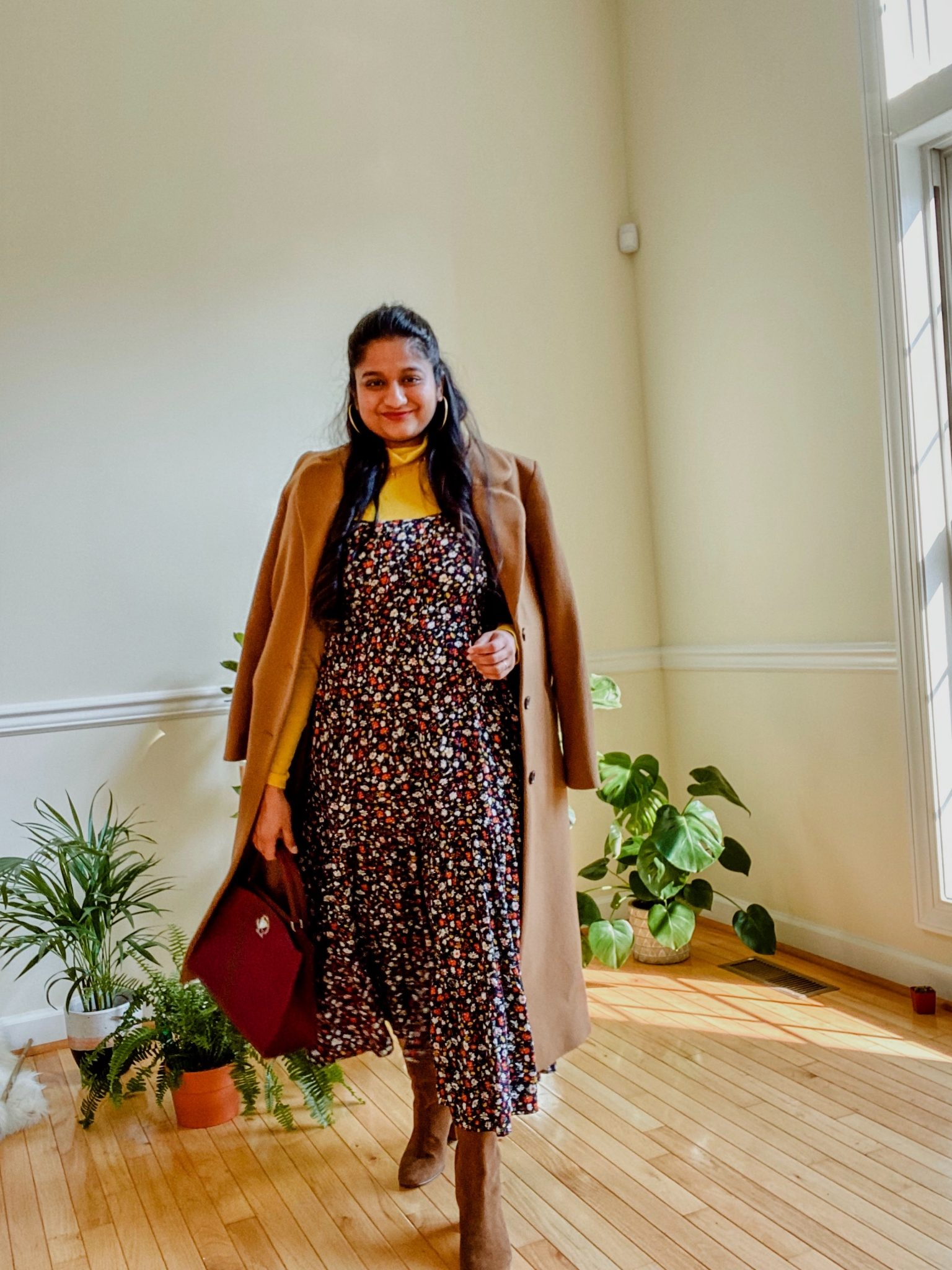 Wearing Ditsy Floral Sleeveless Tiered Midi Dress, Yellow turtleneck sweater, J.Crew Willa suede ankle boots,And other stories camel A-Line Wool Blend Belted Coat 1 |Summer Dresses by popular Maryland modest fashion blog, Dreaming Loud: image of a woman wearing a Know One Cares Ditsy Floral Sleeveless Tiered Midi Dress, J. Crew Tissue turtleneck, & Other Stories Oversized Alpaca Blend Coat, Amazon Kate Spade New York Romy Medium Satchel, and Madewell Oversized Hoop Earrings.
