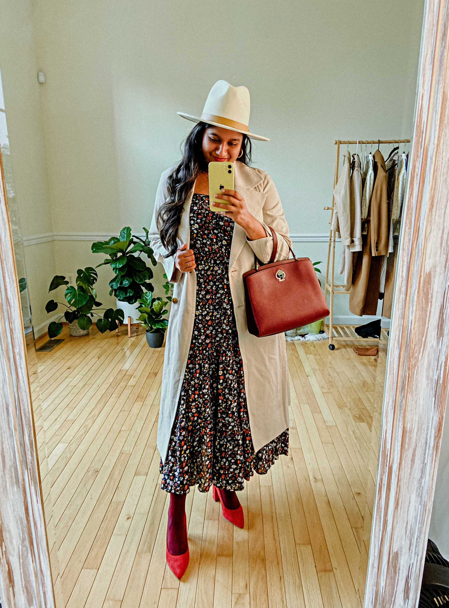 10 Winter Essentials For a Cozy Look featured by top Maryland modest fashion blogger, Dreaming Loud: image of a woman wearing Ditsy Floral Sleeveless Tiered Midi Dress,Everlane trench coat, Lack of Color Fedora hat, burgundy tights