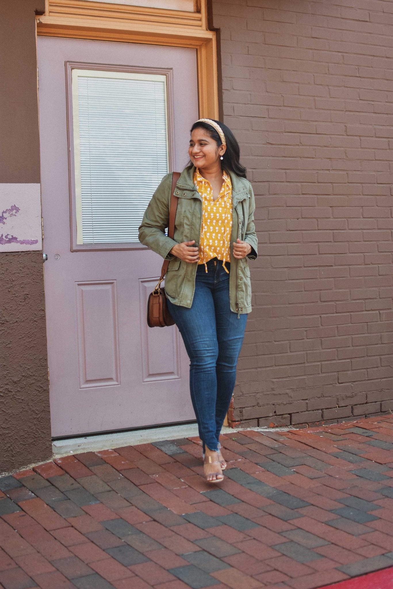 7 Cute Utility jacket Outfits featured by top Maryland fashion blogger, Dreaming Loud: image of a woman wearing J.Crew Ruffle Sleeve Cotton voile top, AG ankle legging jeans, Schutz Ariella mule, Madewell utility Passage Jacket |Utility Jackets by popular Maryland modest fashion blog, Dreaming Loud: image of a woman wearing a utility jacket with a yellow printed blouse and jeans.