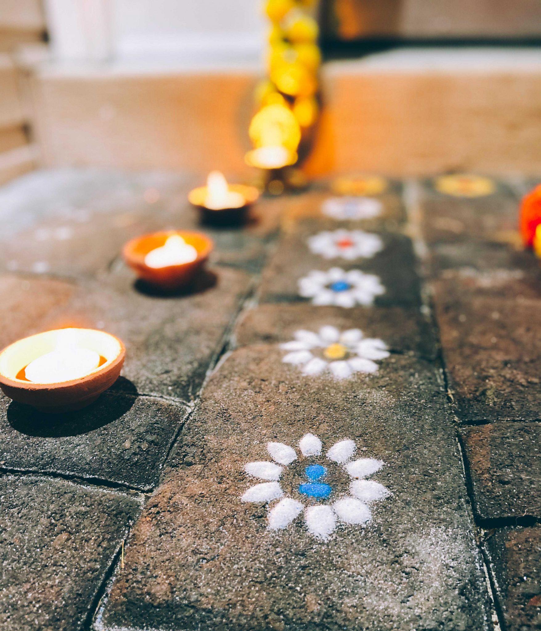 Simple Diwali Decoration ideas featured by top MD lifestyle blogger, Dreaming Loud: Diwali Entrance decoration |Diwali Decoration Ideas: image of a front door and porch decorated with Mango Leaf Toran, Chrysanthemum garlands, Wisteria garlands,Marigold Garlands,Ganesh Diya, Rangoli Stencil, Rangoli Sand Colors, and Clay diyas.